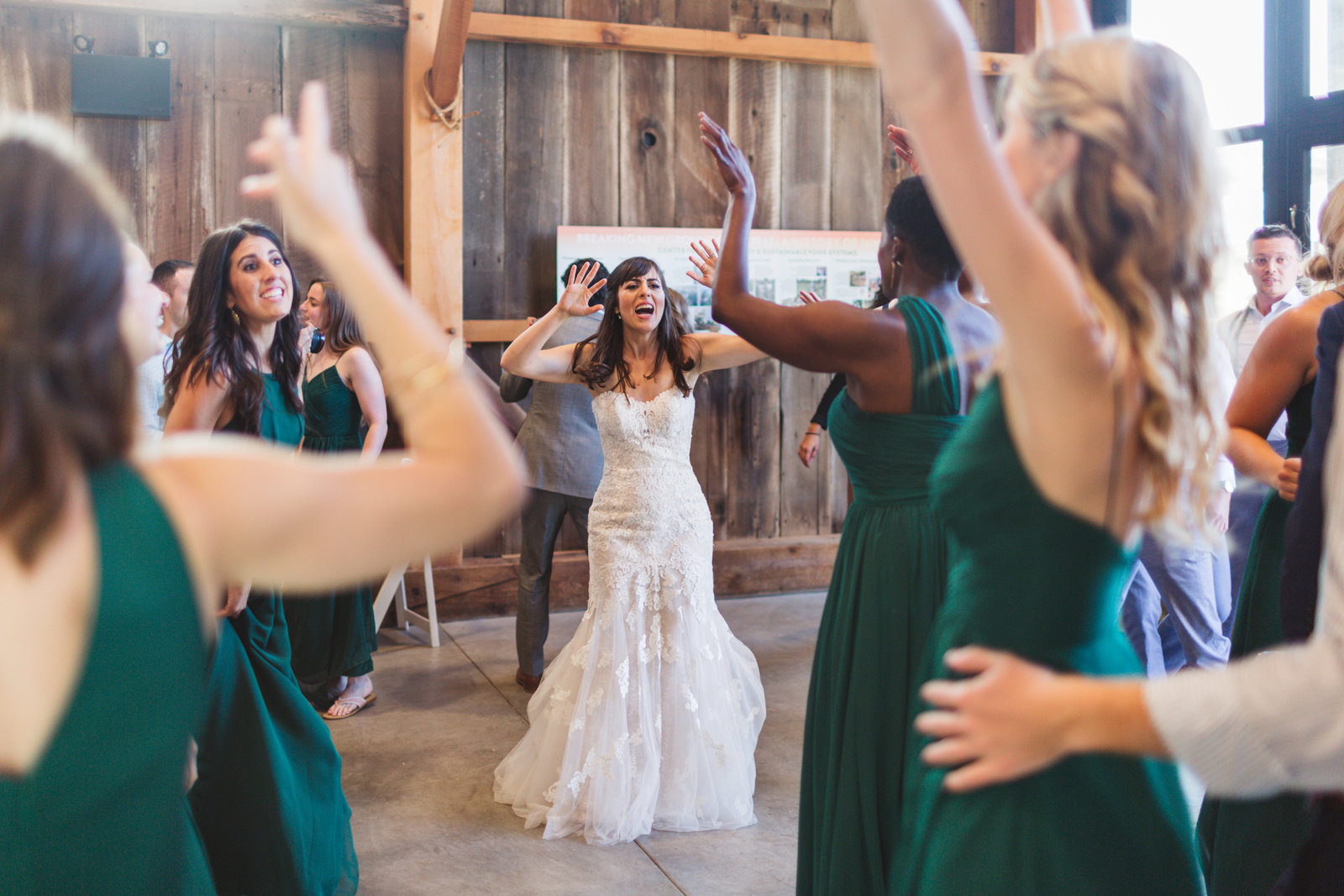 UCSC barn wedding with bride dancing between bridesmaids in green dresses
