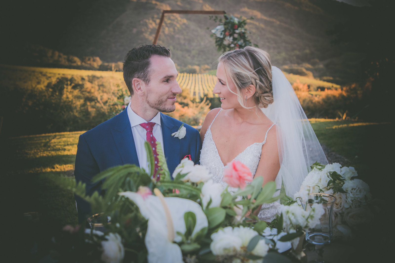 Bride and groom smile at each other at table during sunset in Carmel Highlands.