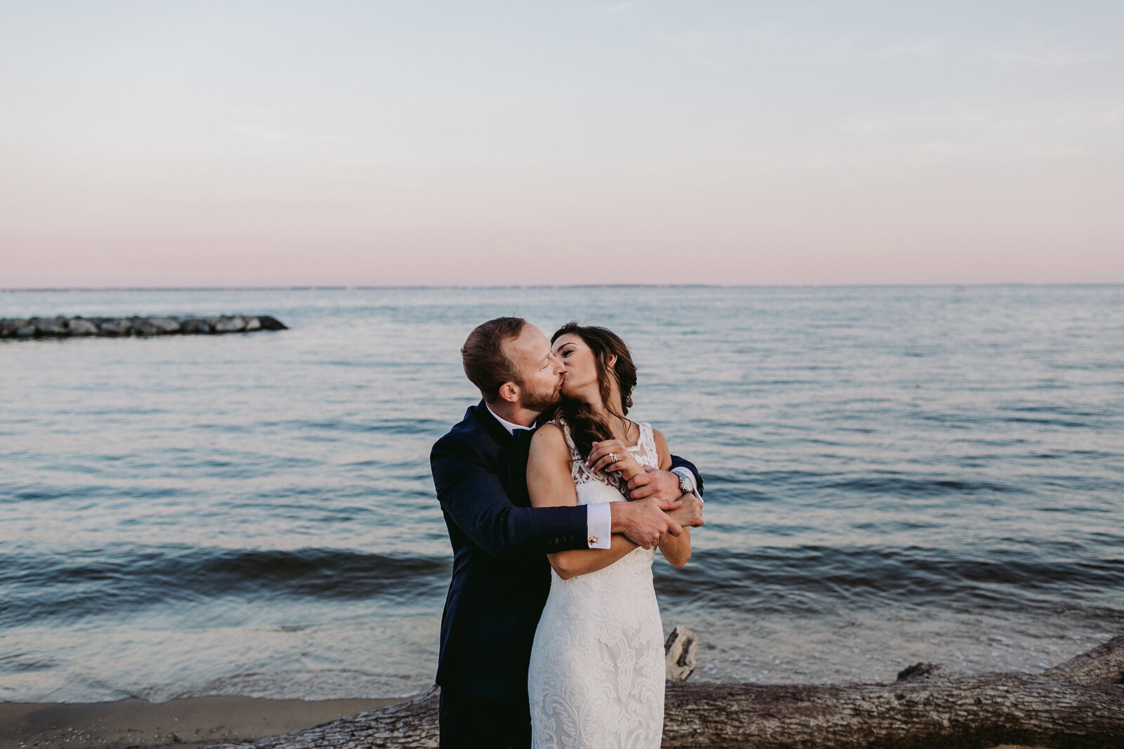bride and groom kissing at beach sunset