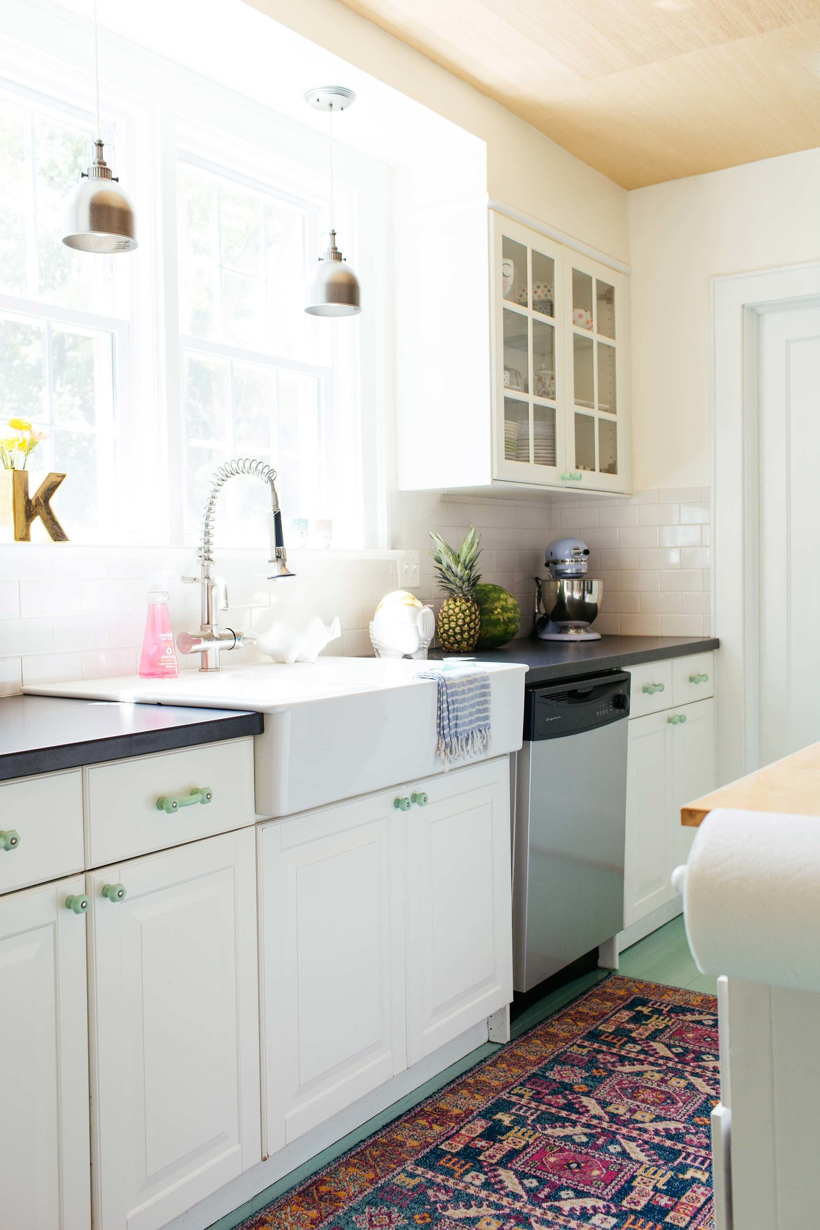 A small kitchen with mint floors and white cabinets.