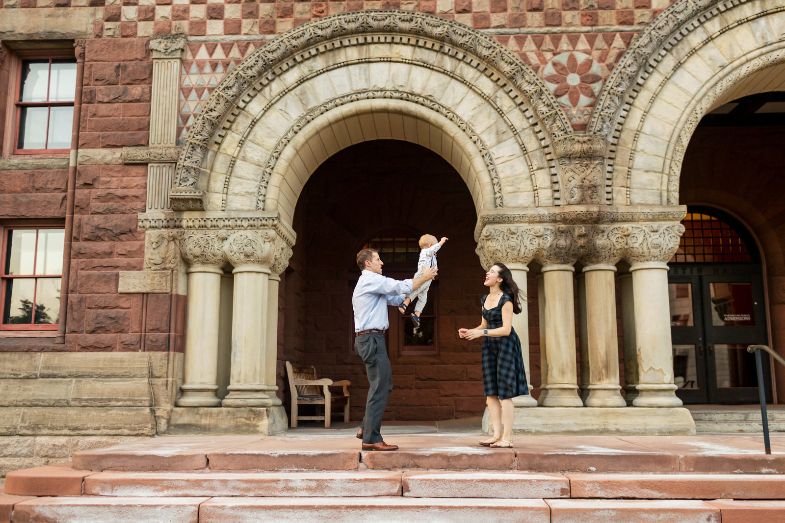 dad flies little boy to mom in front of harvard building during cambridge family session