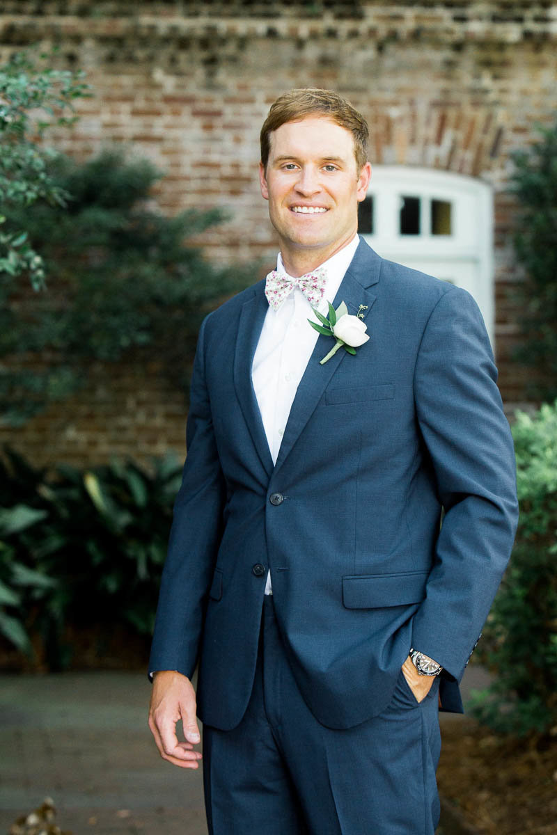 Groom stands in front of the Rice Mill Building, Charleston, South Carolina. Kate Timbers Photography.
