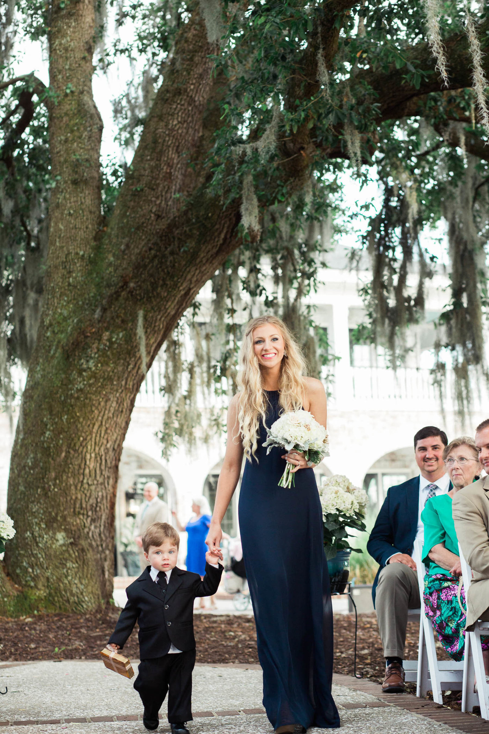 Bridesmaid and ring bearer walk down the aisle, Dunes West Golf and River Club, Charleston Wedding Photographer.