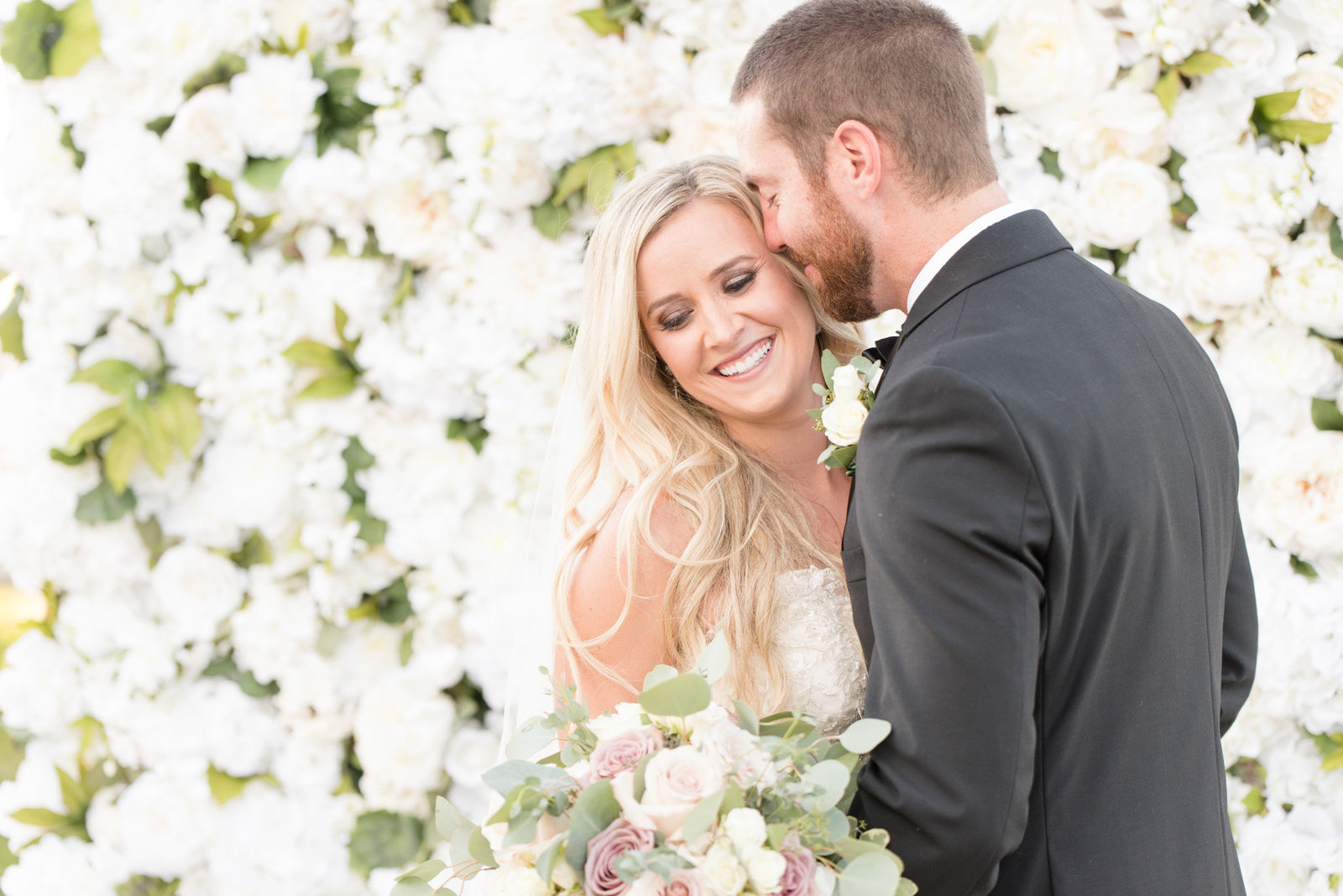 Bride and groom snuggle in front of flower wall.