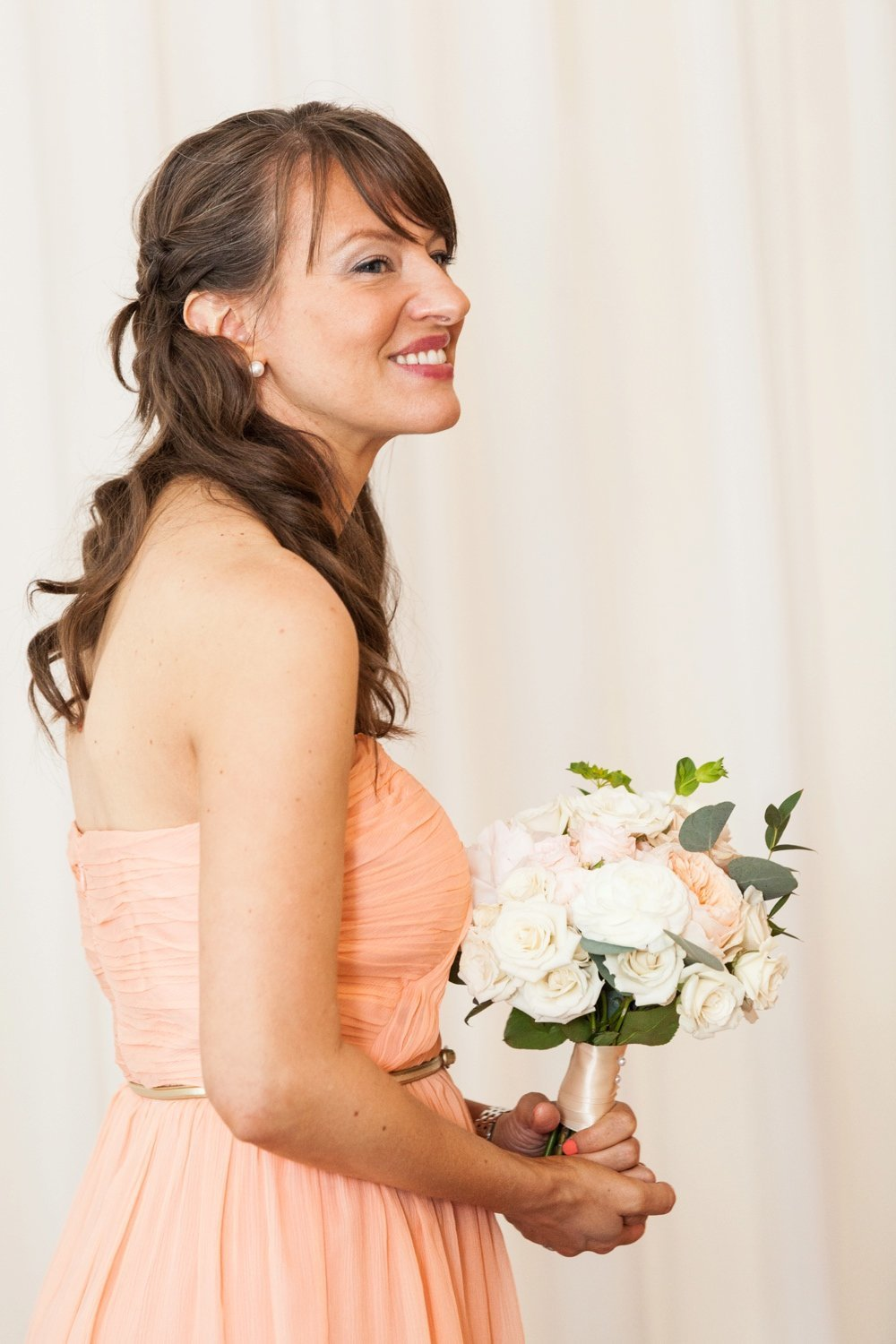 Gorgeous bridesmaid in coral dress with bouquet