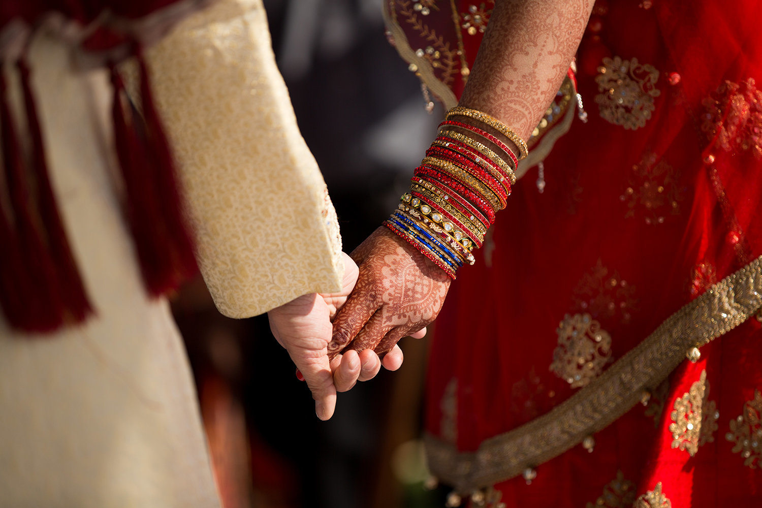 Close up of a bride and groom's hands during a Hindu wedding ceremony