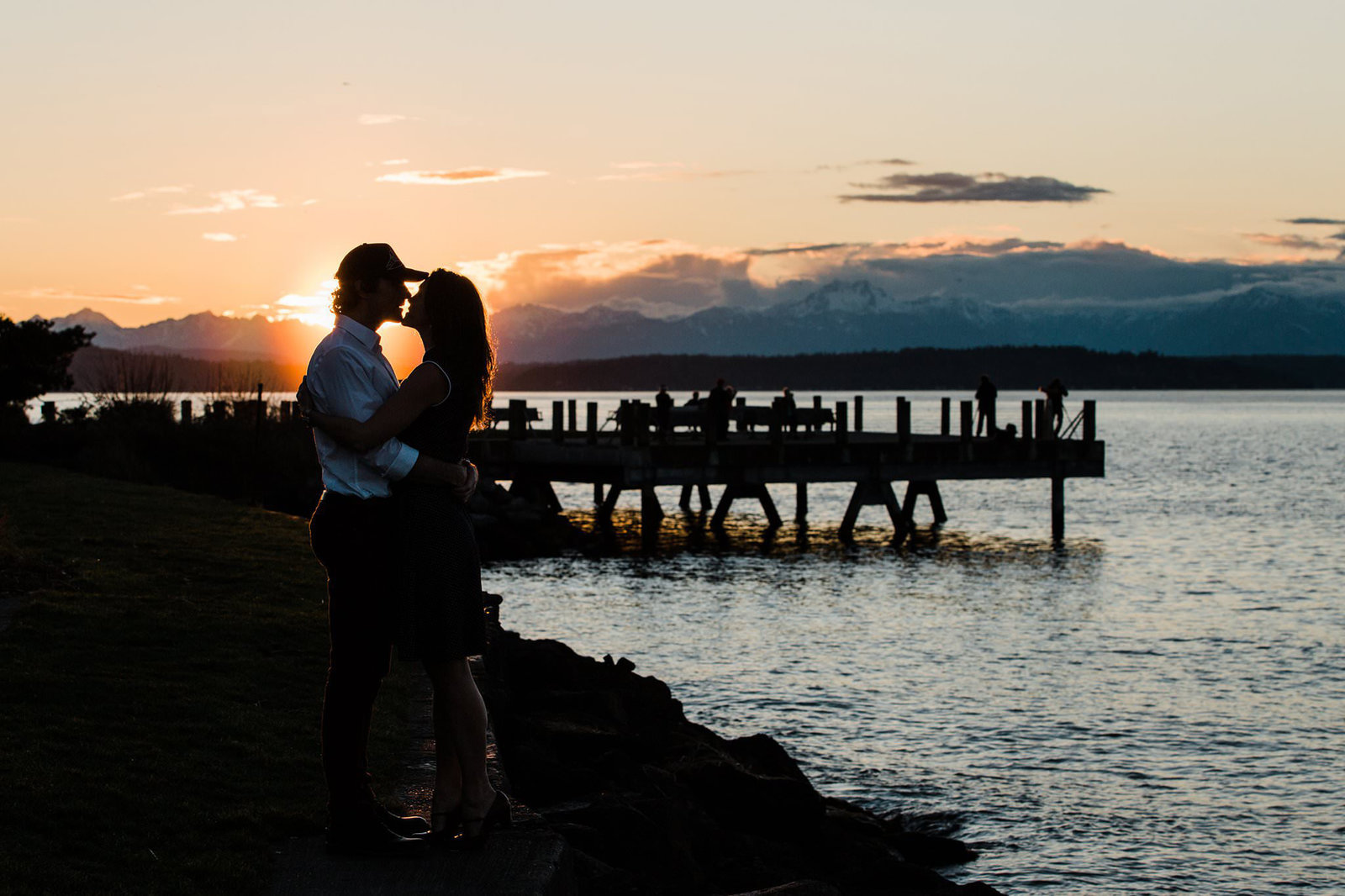 A couples enjoys a stunning sunset on the beach in West Seattle during their engagement session with Seattle elopement photographer Amy Galbraith