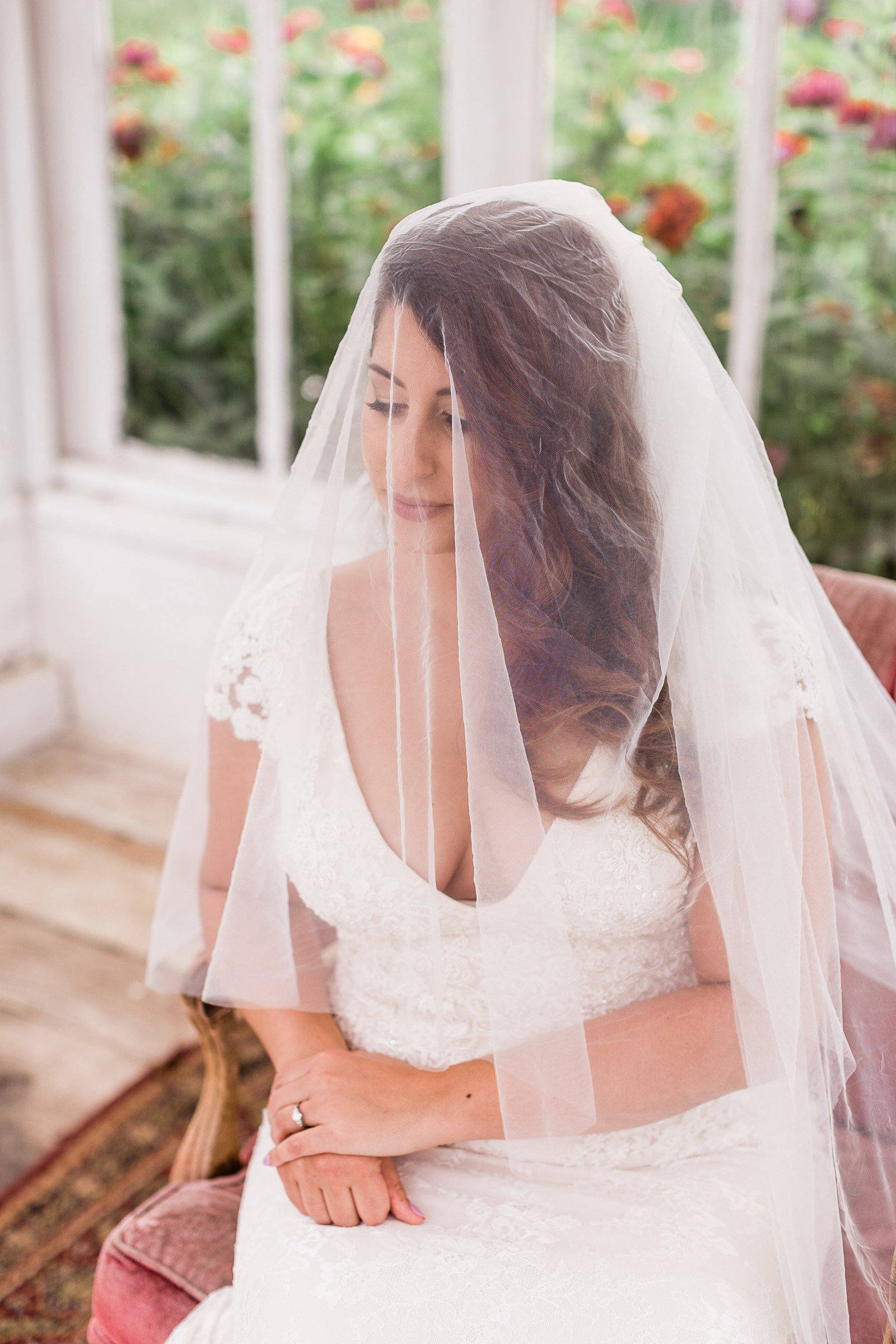 Bride sitting in a greenhouse, for bridal portrait with veil over her head. Hollywood Glamor. Luxoumont Farm PA