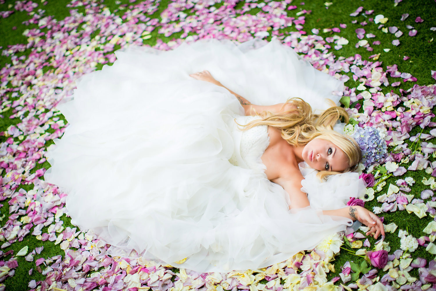 Amazing bridal portrait of bride laying on a bed of rose petals