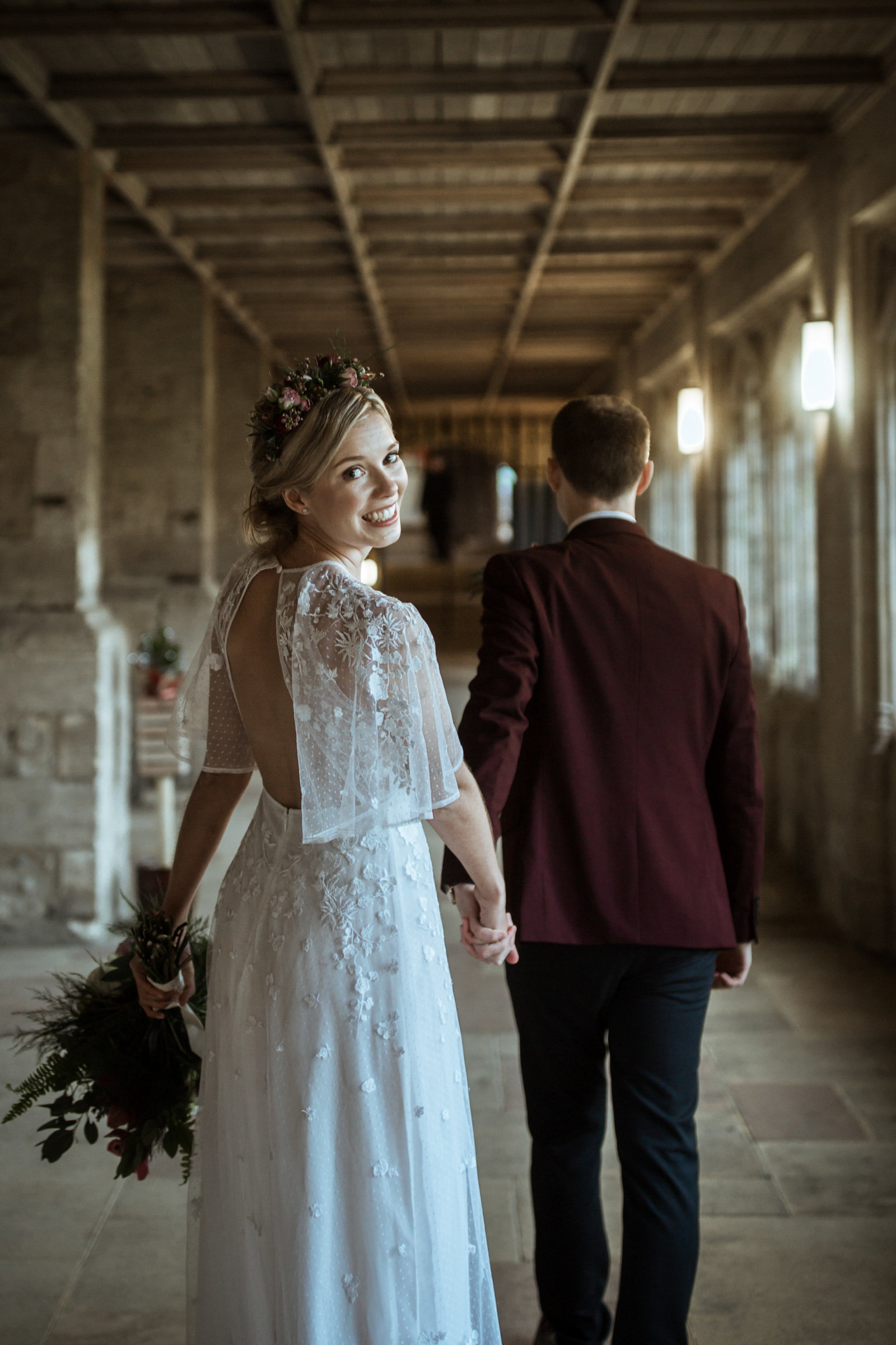 A smiling Bride looks back over her shoulder while walking in a Cathedral cloister in Norfolk.