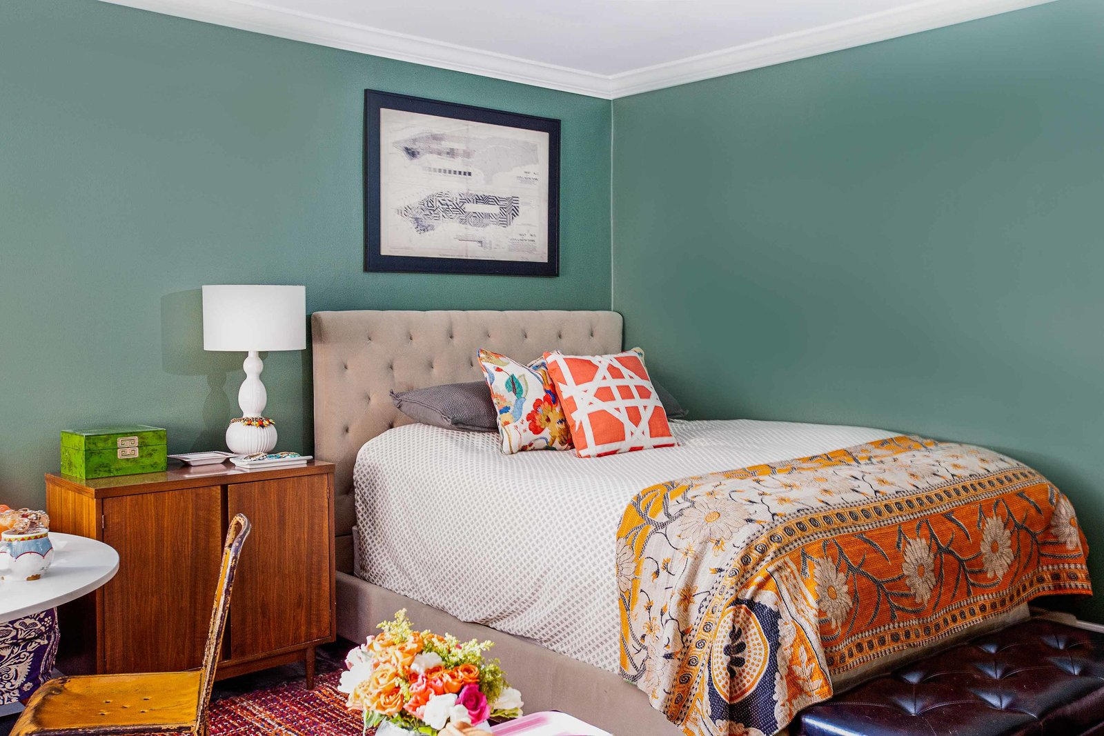 A bed with a tufted headboard and sideboard end table.