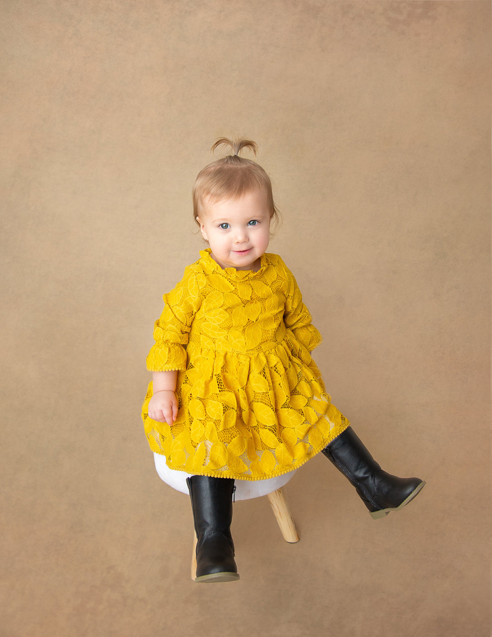 In studio milestone session - one year old, sitting on a small chair, wearing black boots and a gold dress