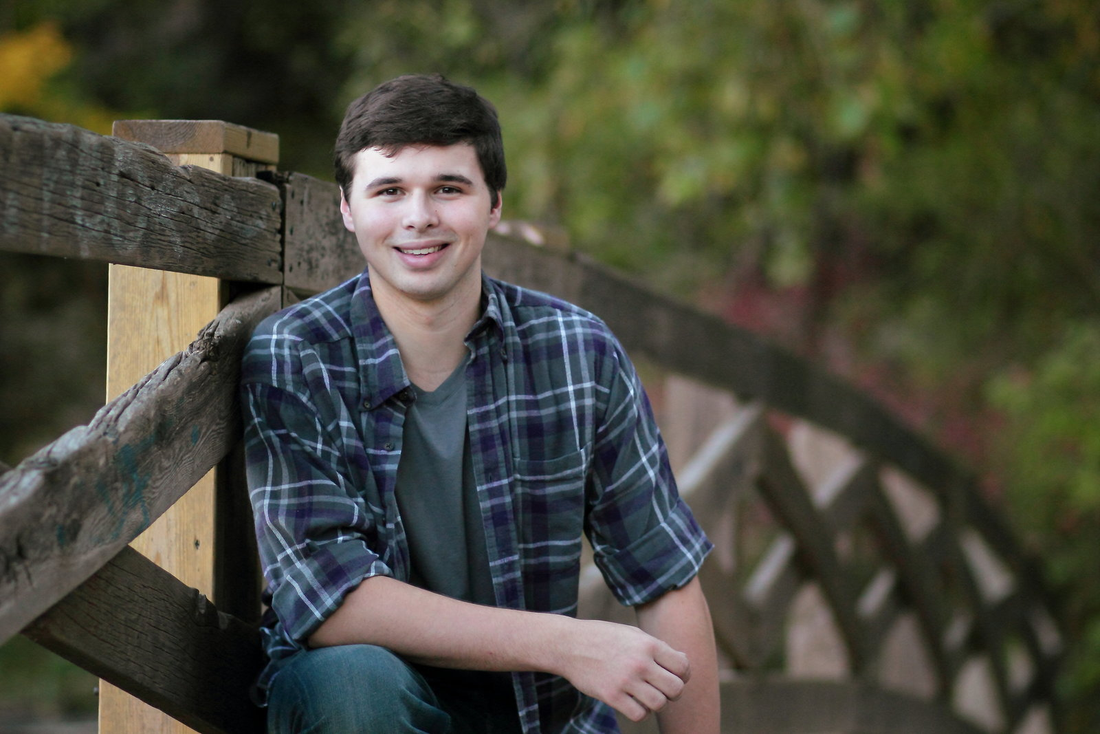 Senior portraits of a guy on wooden bridge