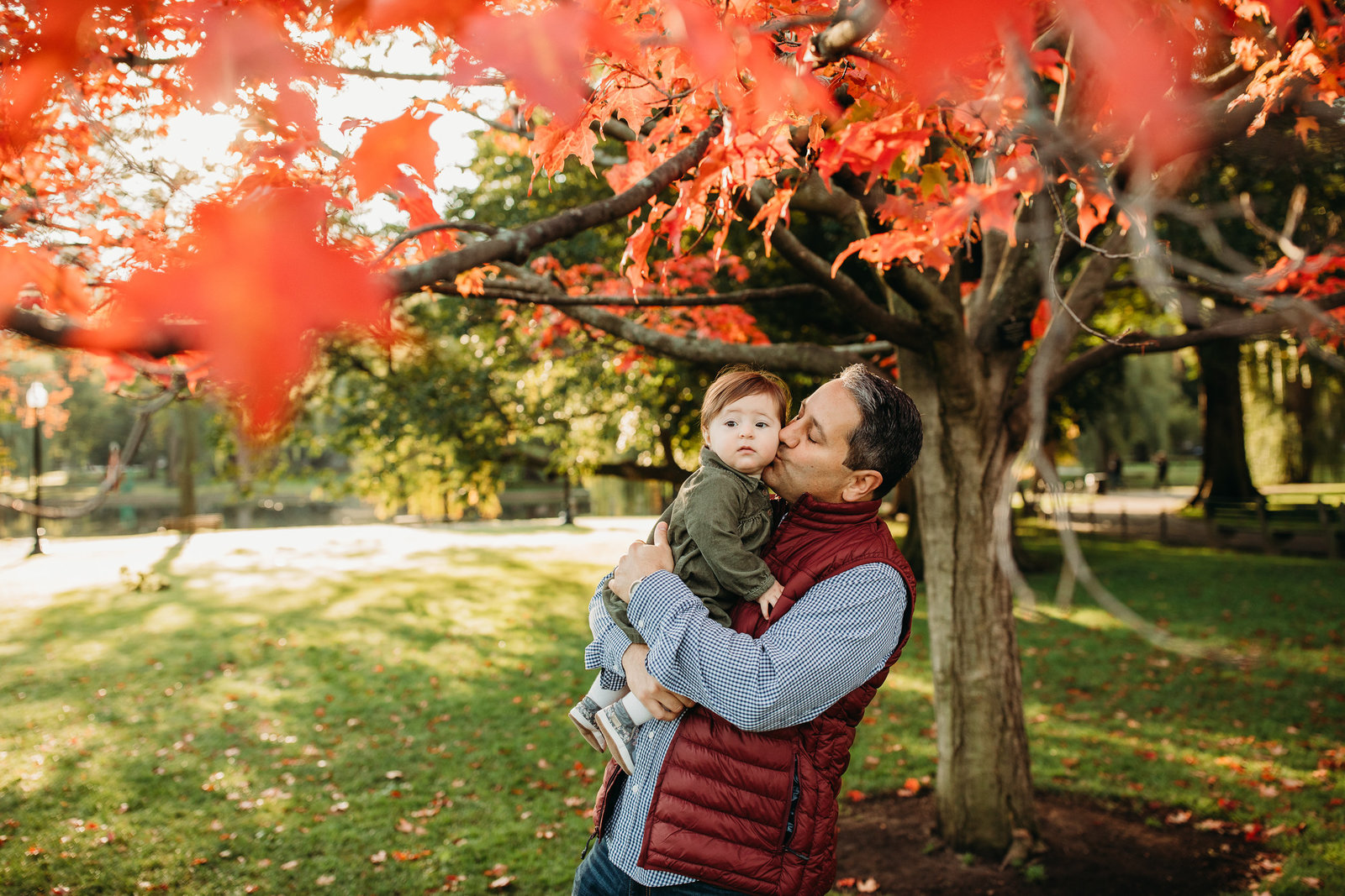 father holds baby girl under red autumn leaves during family photo session in boston