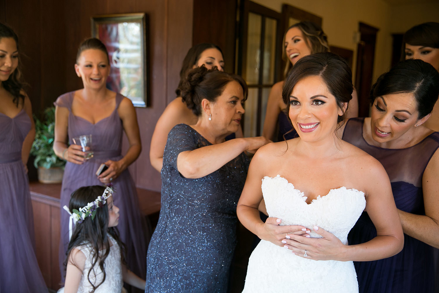 bride putting dress on with friends