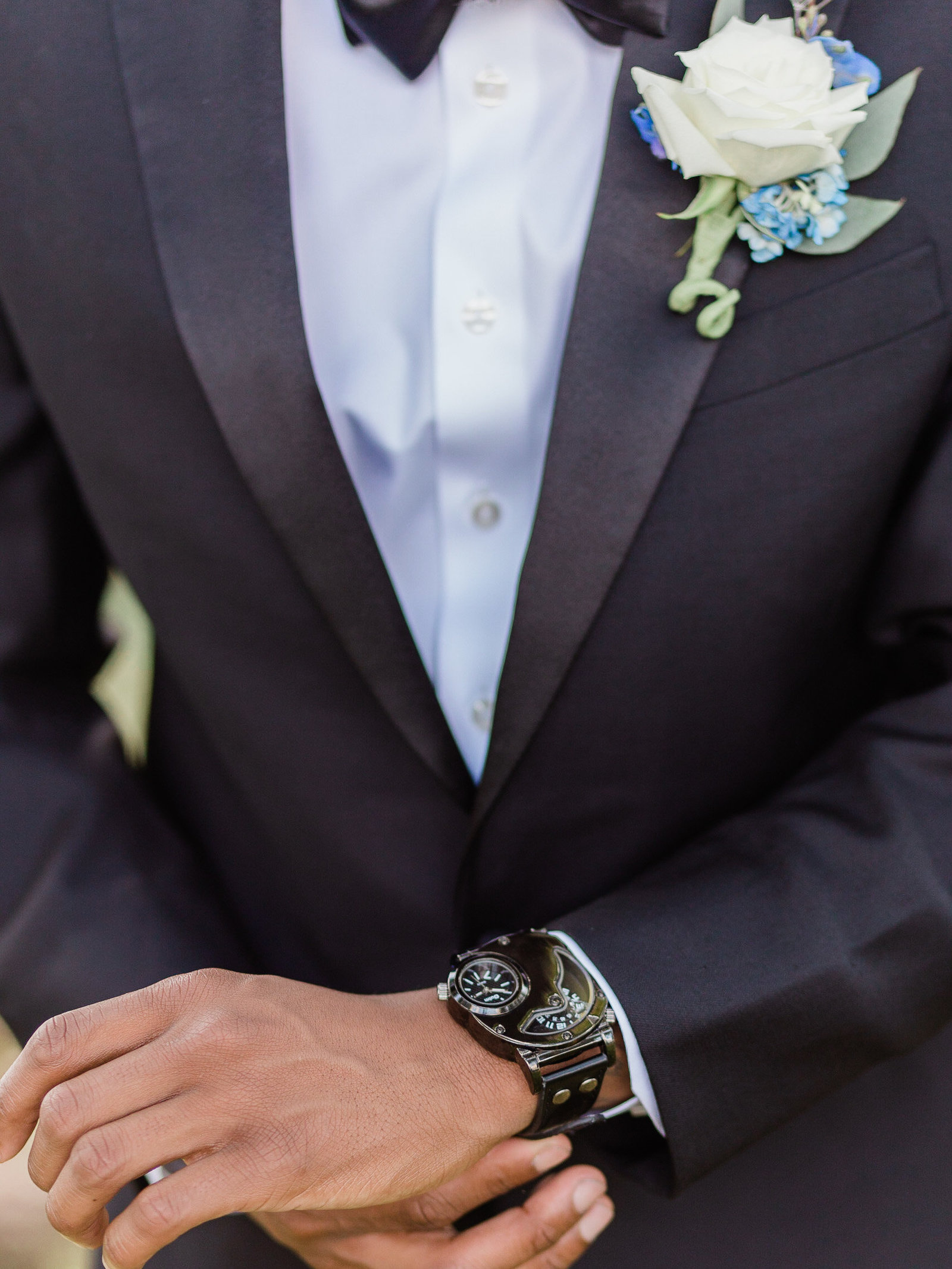 Close up of African American groom in a black suit with white rose boutonniere, adjusting his watch