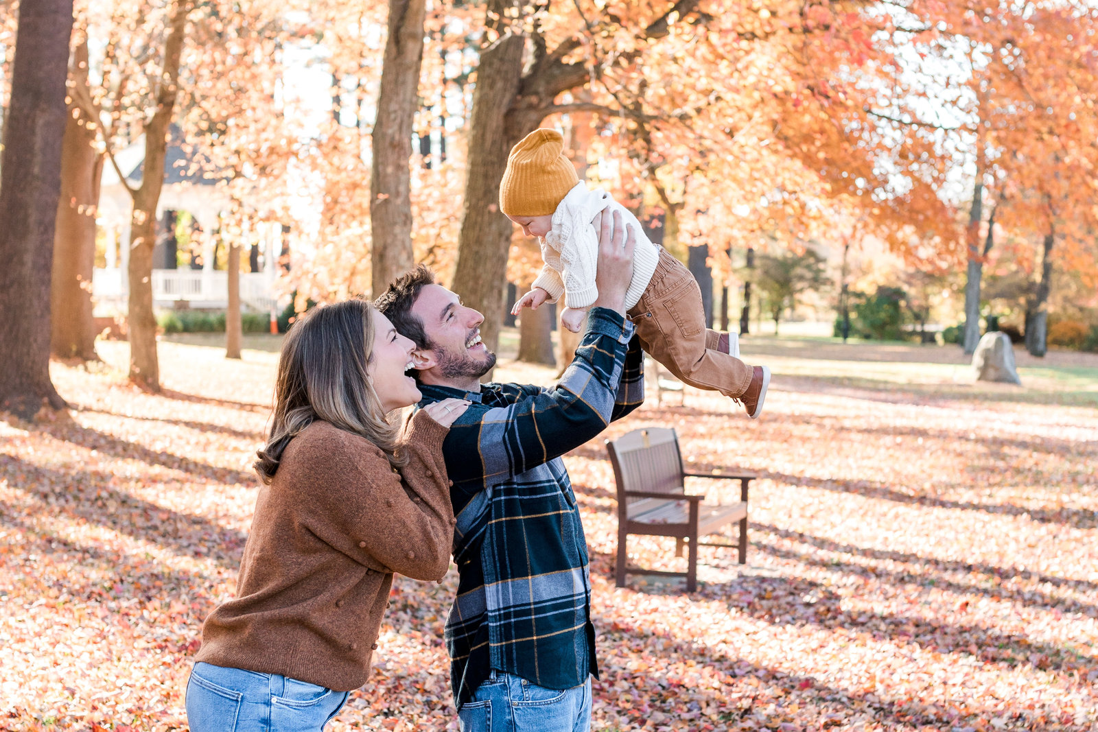 Couple throwing their son in the air for a photo at Wampus Brook Park, Armonk