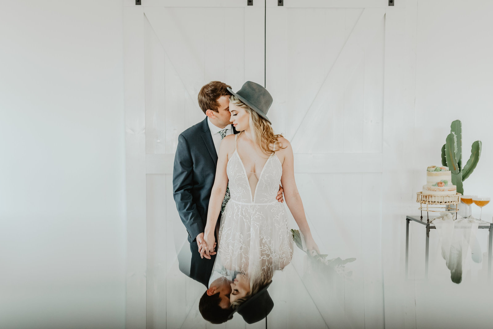 Groom kisses Bride while holding hands in front of barn doors at 14 Tenn