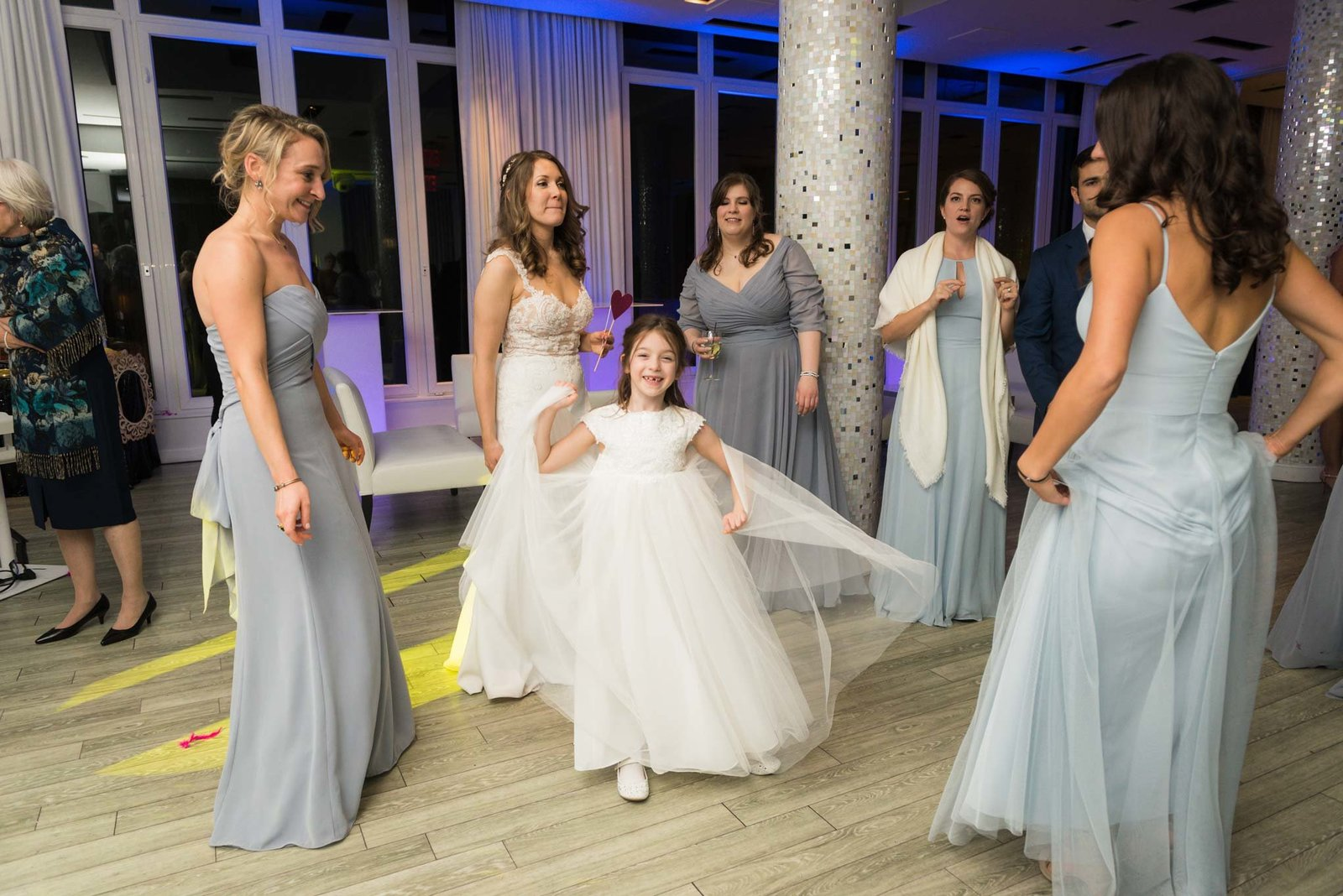 Bride, bridesmaids, and flower girl dancing at  Allegria Hotel