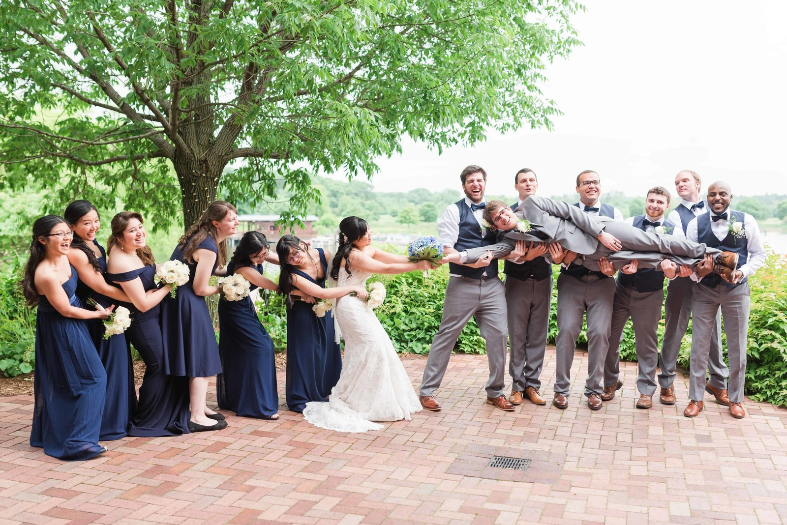 Bride and Groom playing tug of war with bridal party