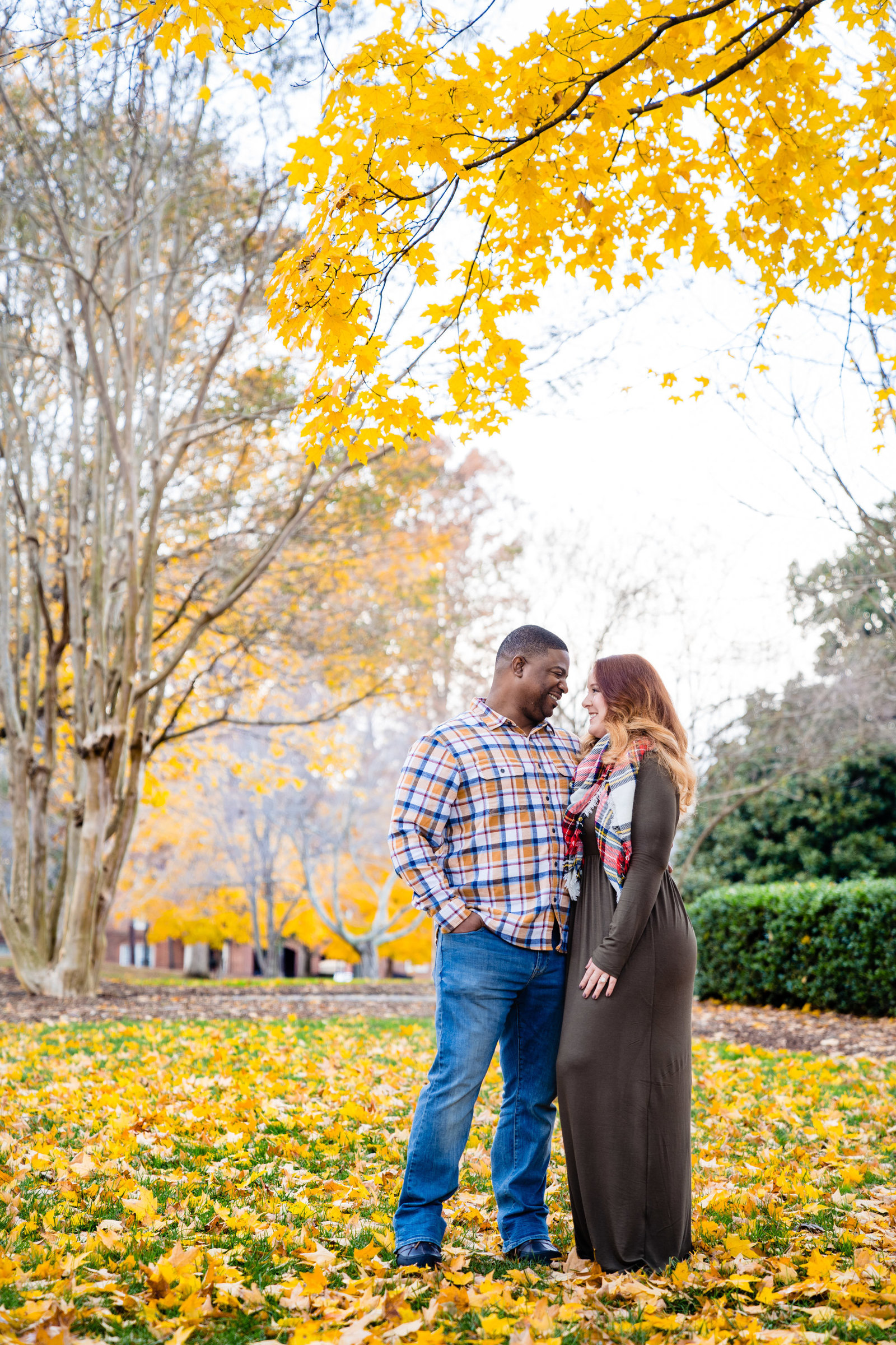 couple standing under yellow tree