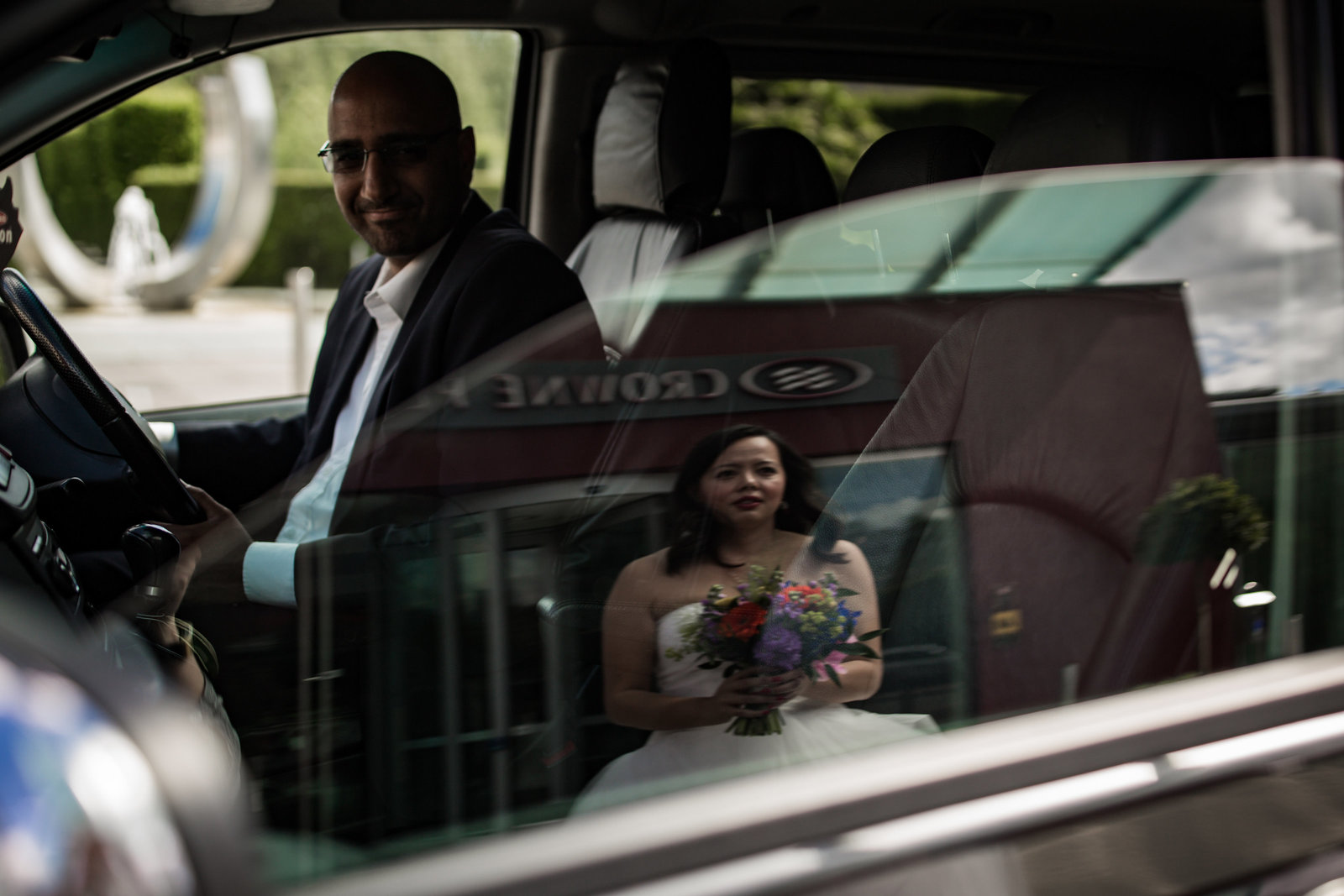 A bride is photographed in the reflection of a car window as the taxi driver smiles at her.