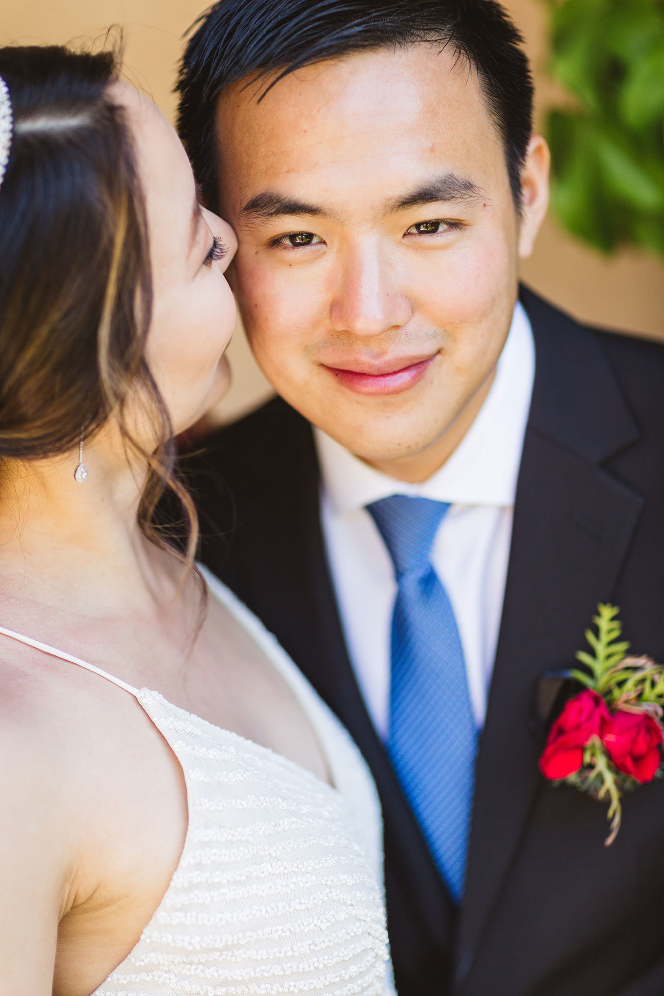 dapper groom with red boutonniere smiles at camera