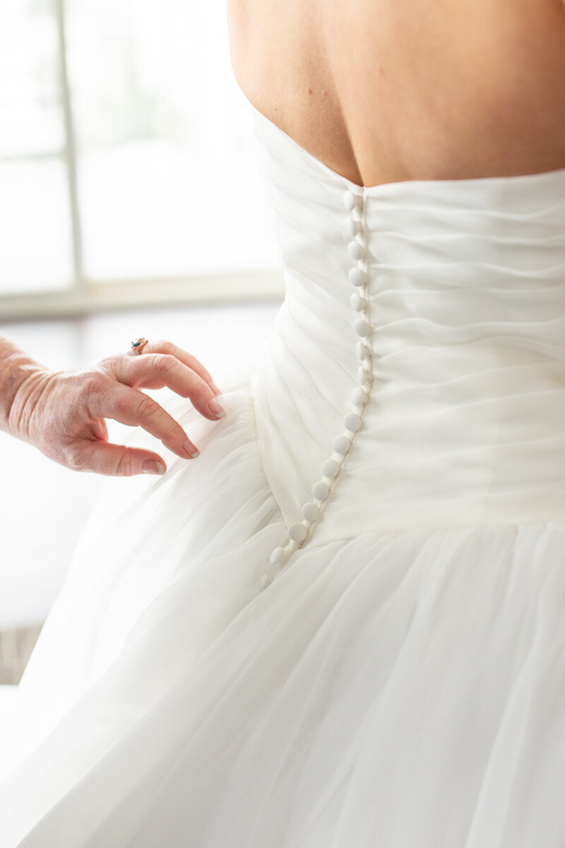 close up photo of mom of bride buttoning up bridal gown