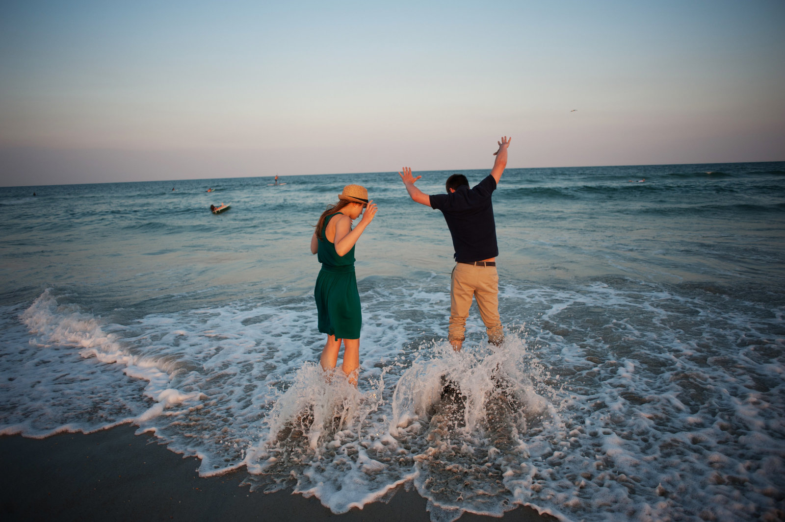 an engaged couple get too close to the ocean and get wet