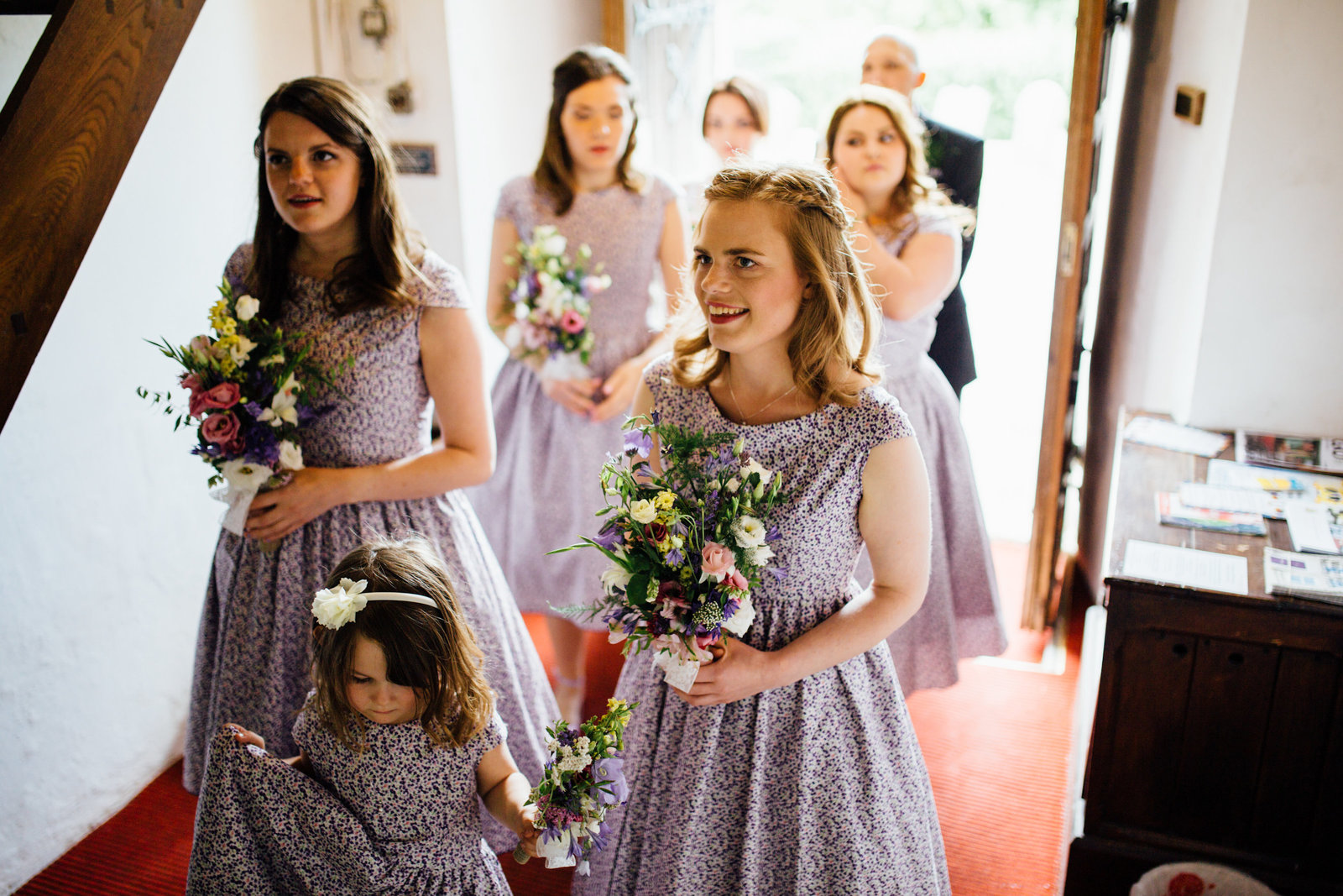 Purple bridesmaids excited to enter church wedding ceremony in rural Suffolk