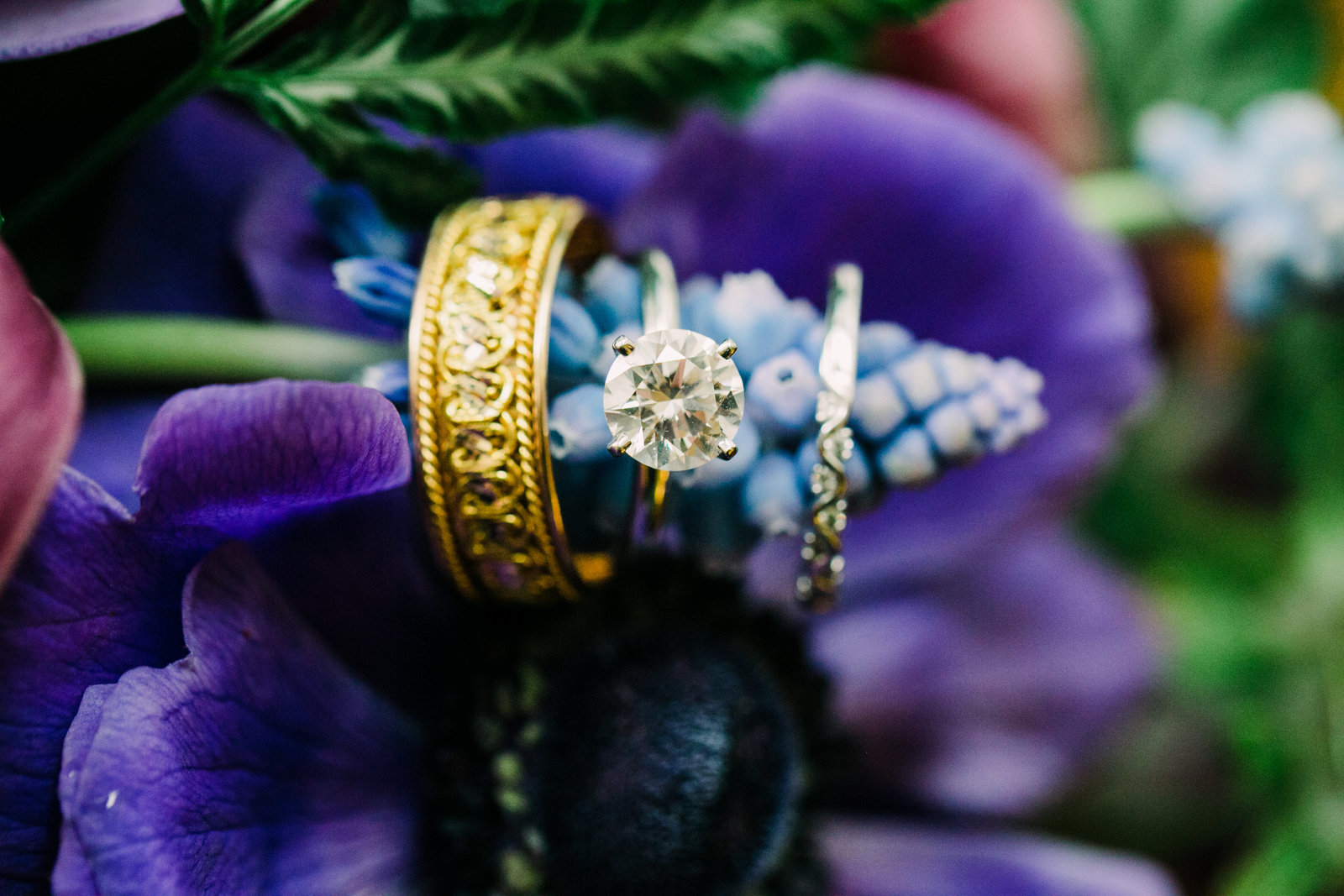 This is a detail photo of wedding rings on a blue and purple flower