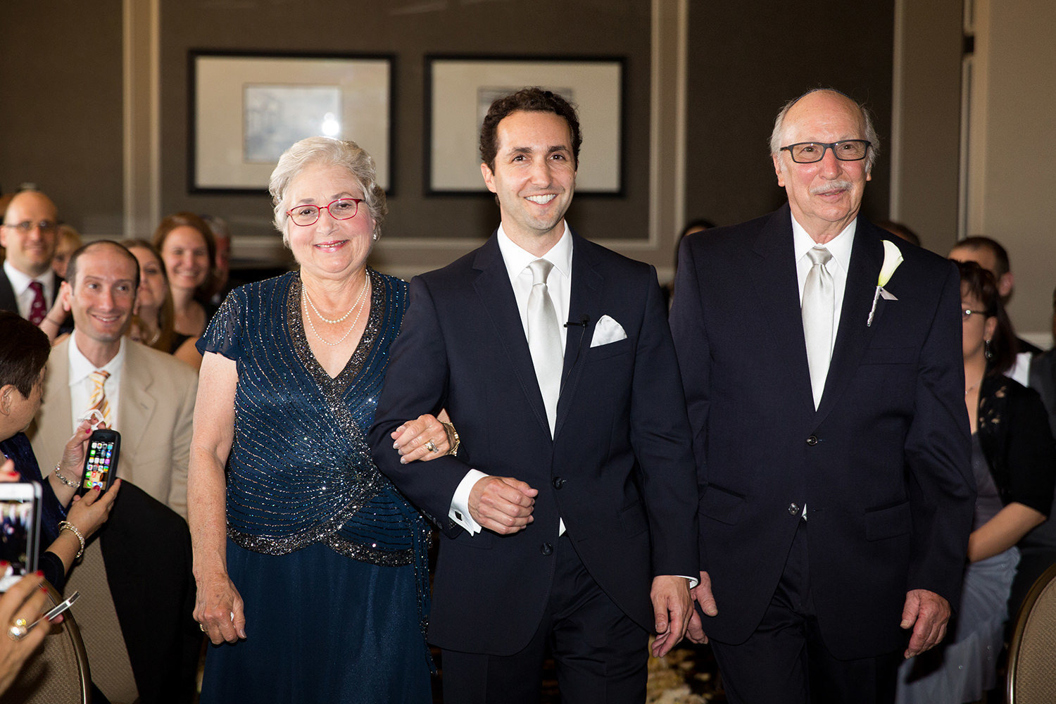 groom with parents walking down the aisle