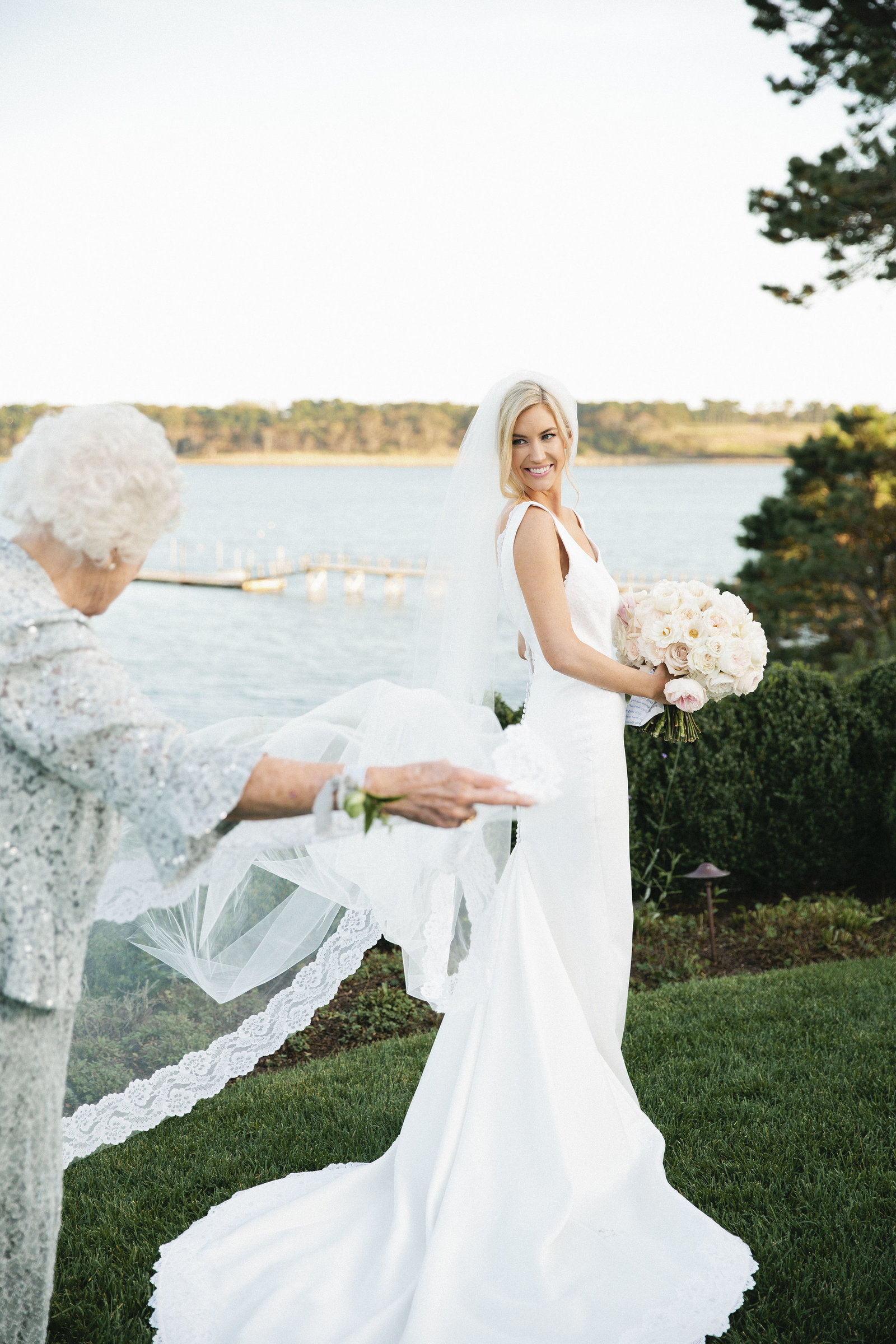 Whitney BIschoff's grandmother fluffing the bride's dress and holding the bride's train