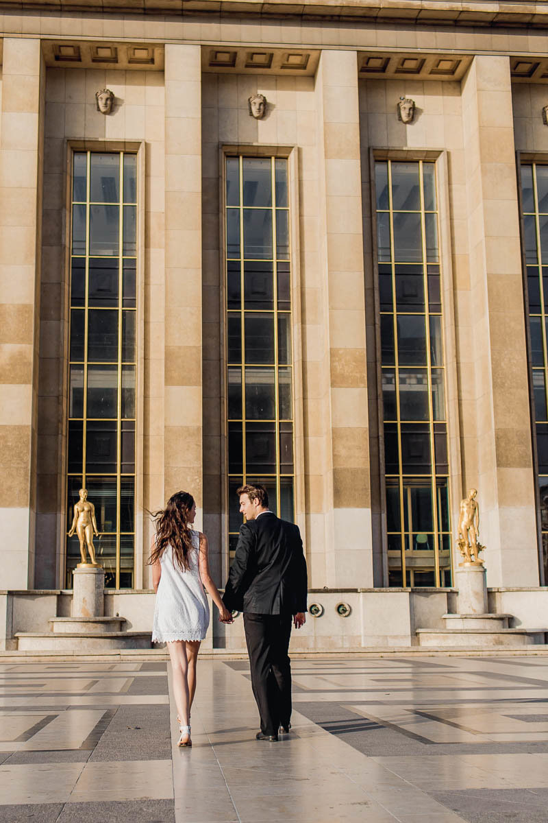 Bride and groom walk in the plaza between gold statues, Palais de Chaillot, Paris, France