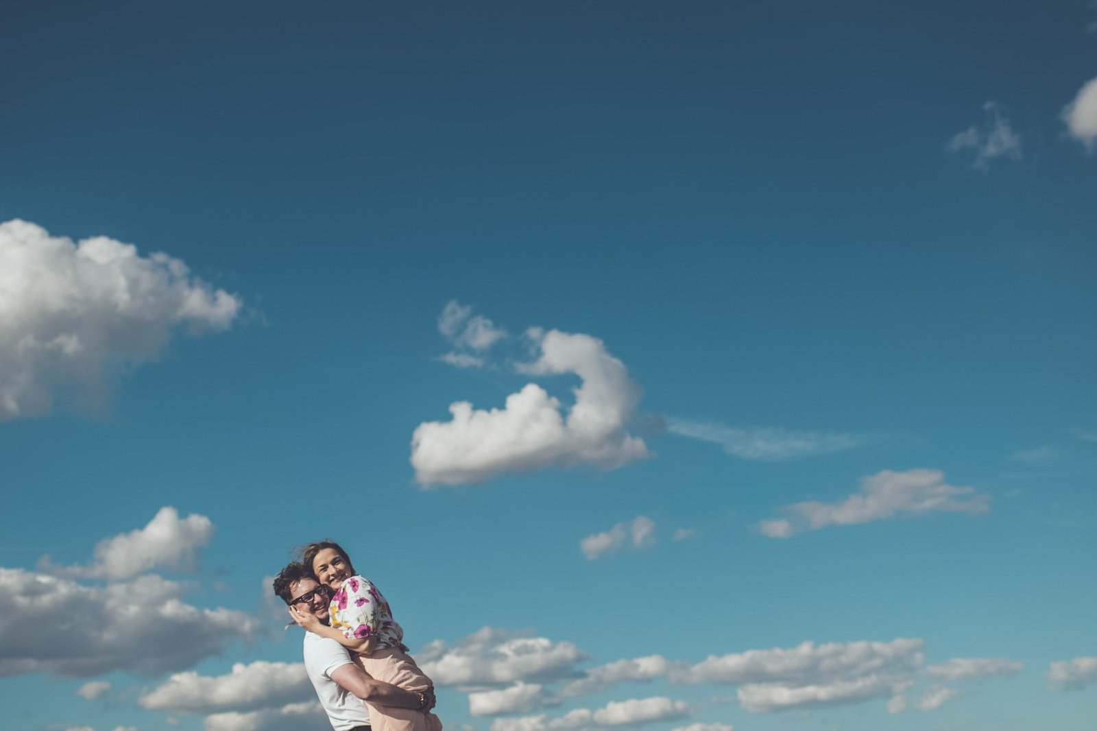 An engaged couple hug against a puffy clouded blue sky in Norfolk. They're looking at the camera and smiling.