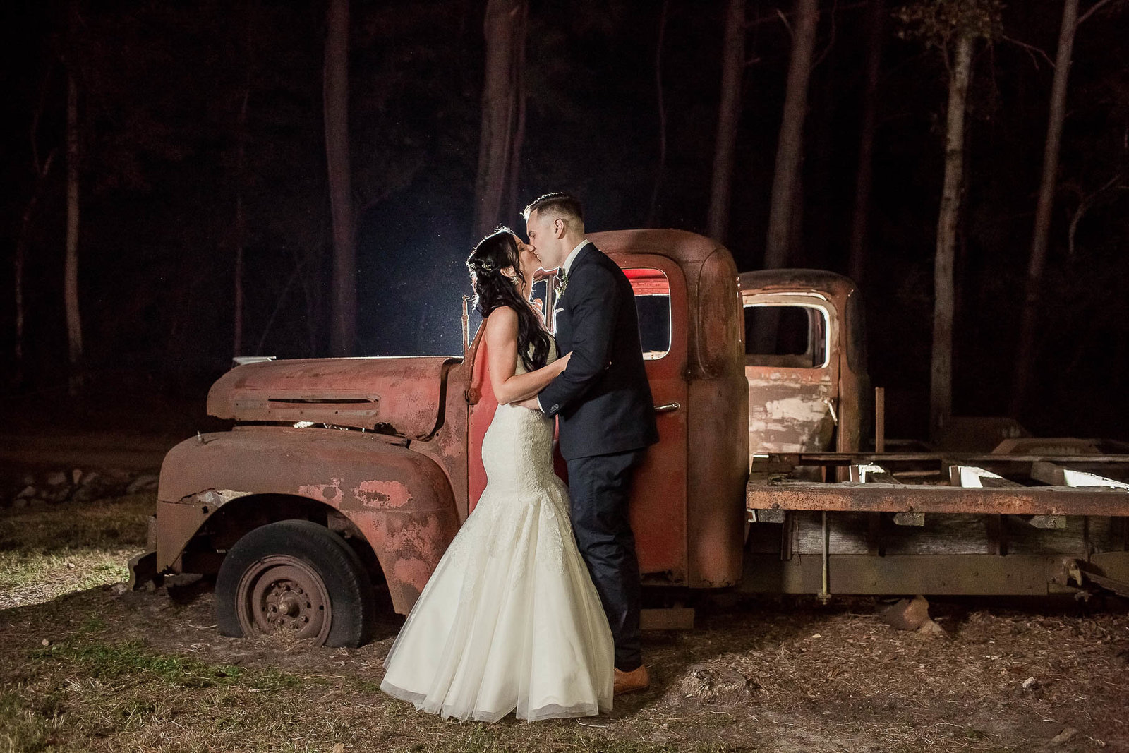 Bride and groom pose by red rustic truck at night, Boals Farm, Charleston, South Carolina