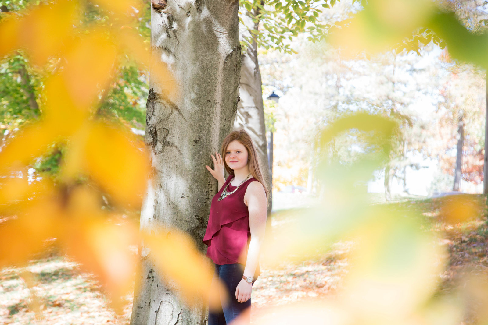 senior leans against a tree surrounded by fall foliage in robin hill park