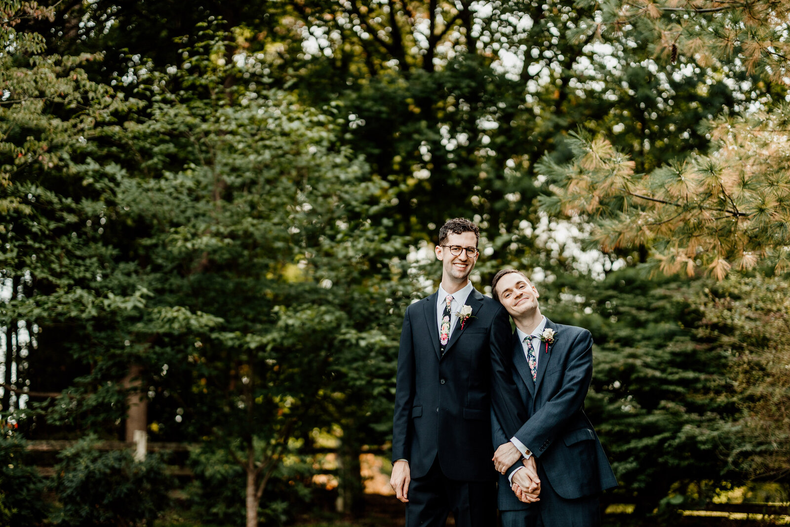 gay grooms holding hands in trees