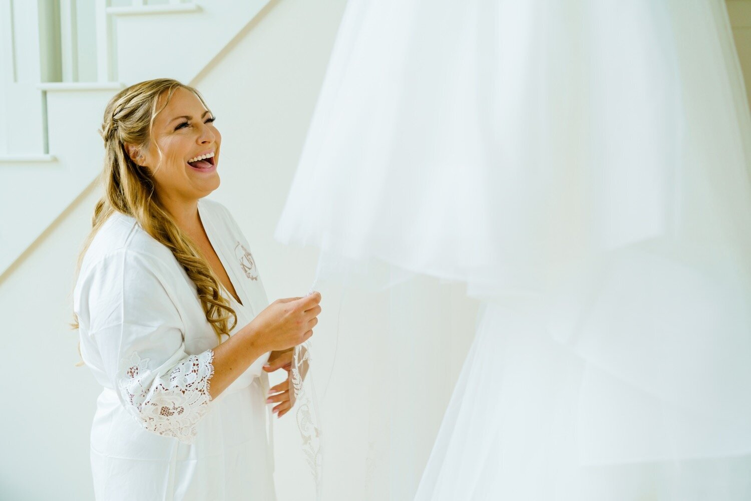 New Hampshire Bride laughing and smiling up at wedding dress