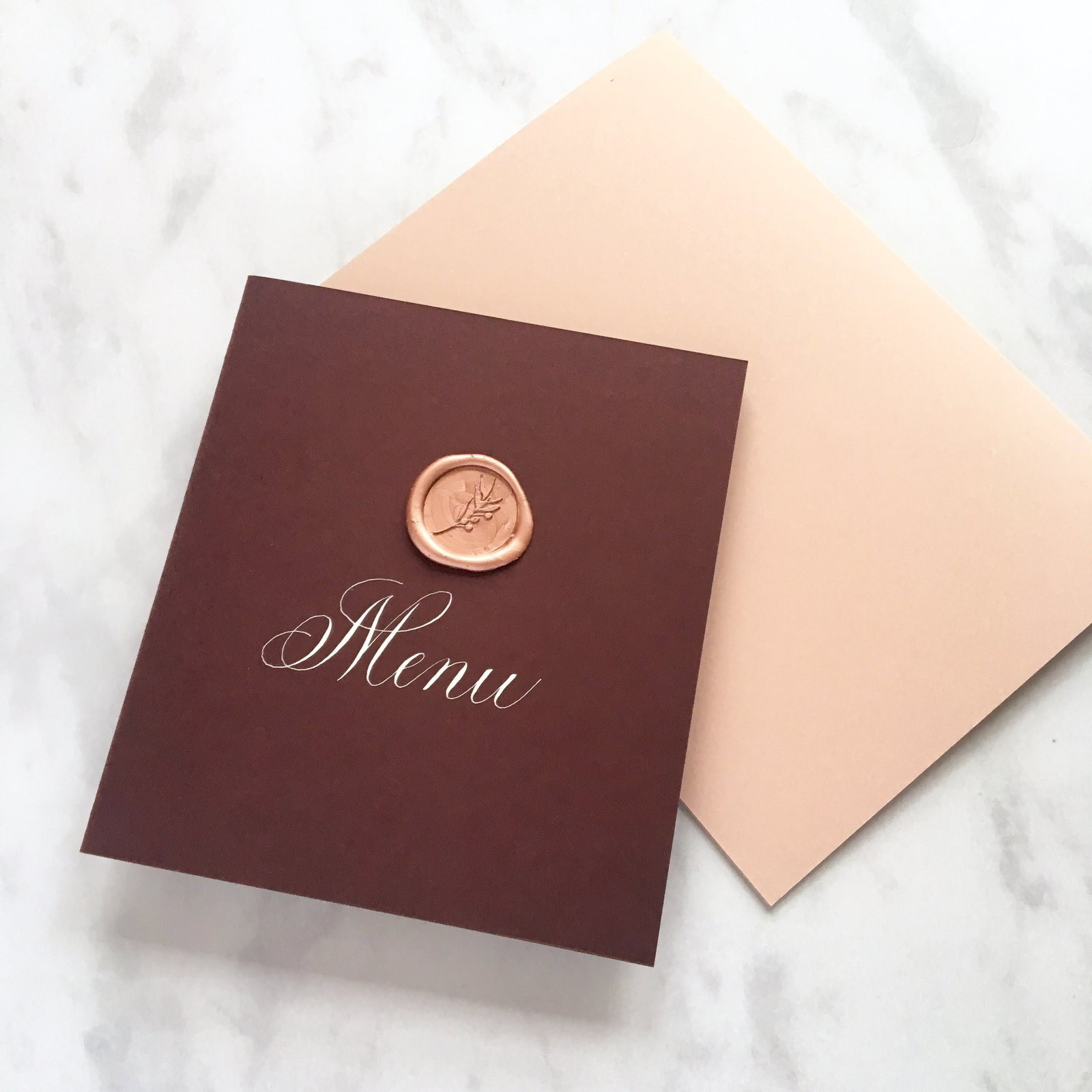 Menu booklets with white calligraphy and wax seal