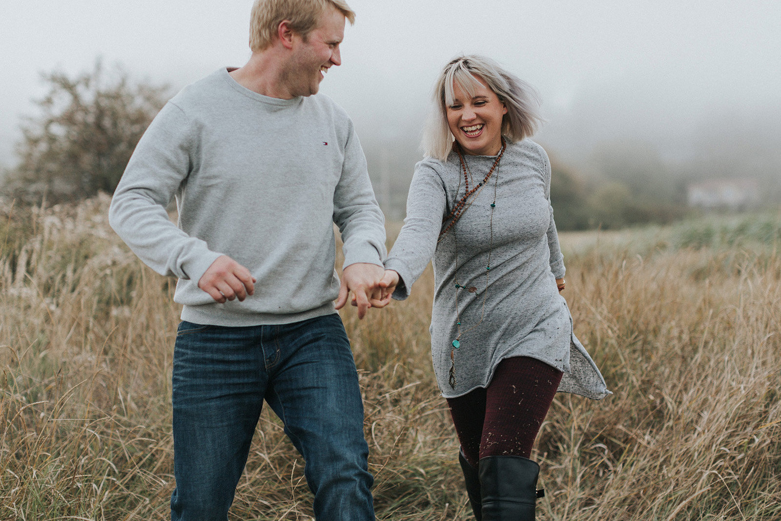 Fun couple running through a field in Victoria BC