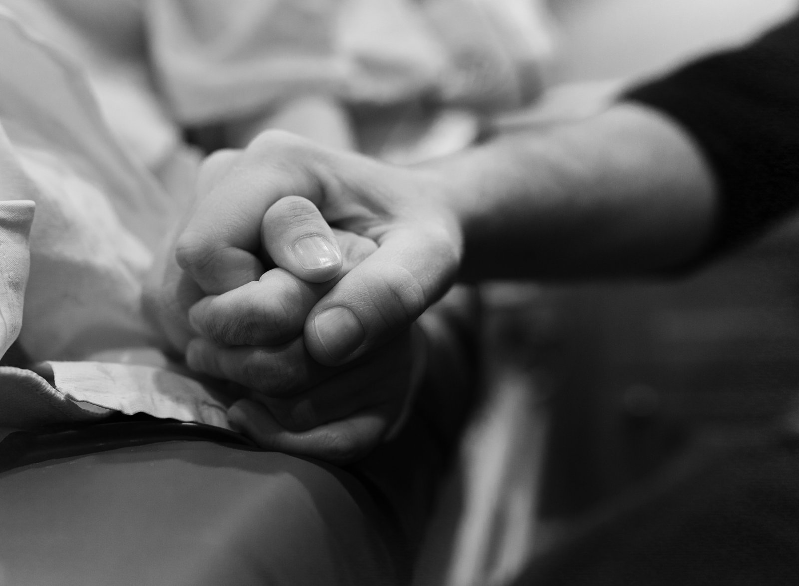 charlotte birth photographer jamie lucido captures a beautiful and powerful image of mother and father holding hands during the birth of their child