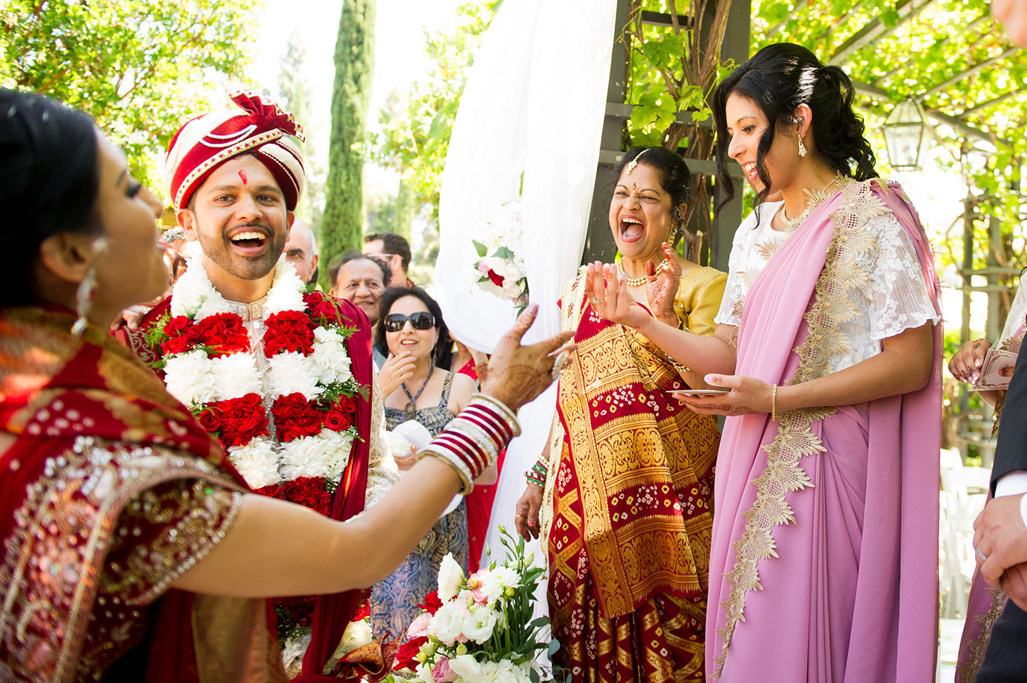 The groom bargains with bridesmaids to get his shoes back after a traditional hindu wedding ceremony