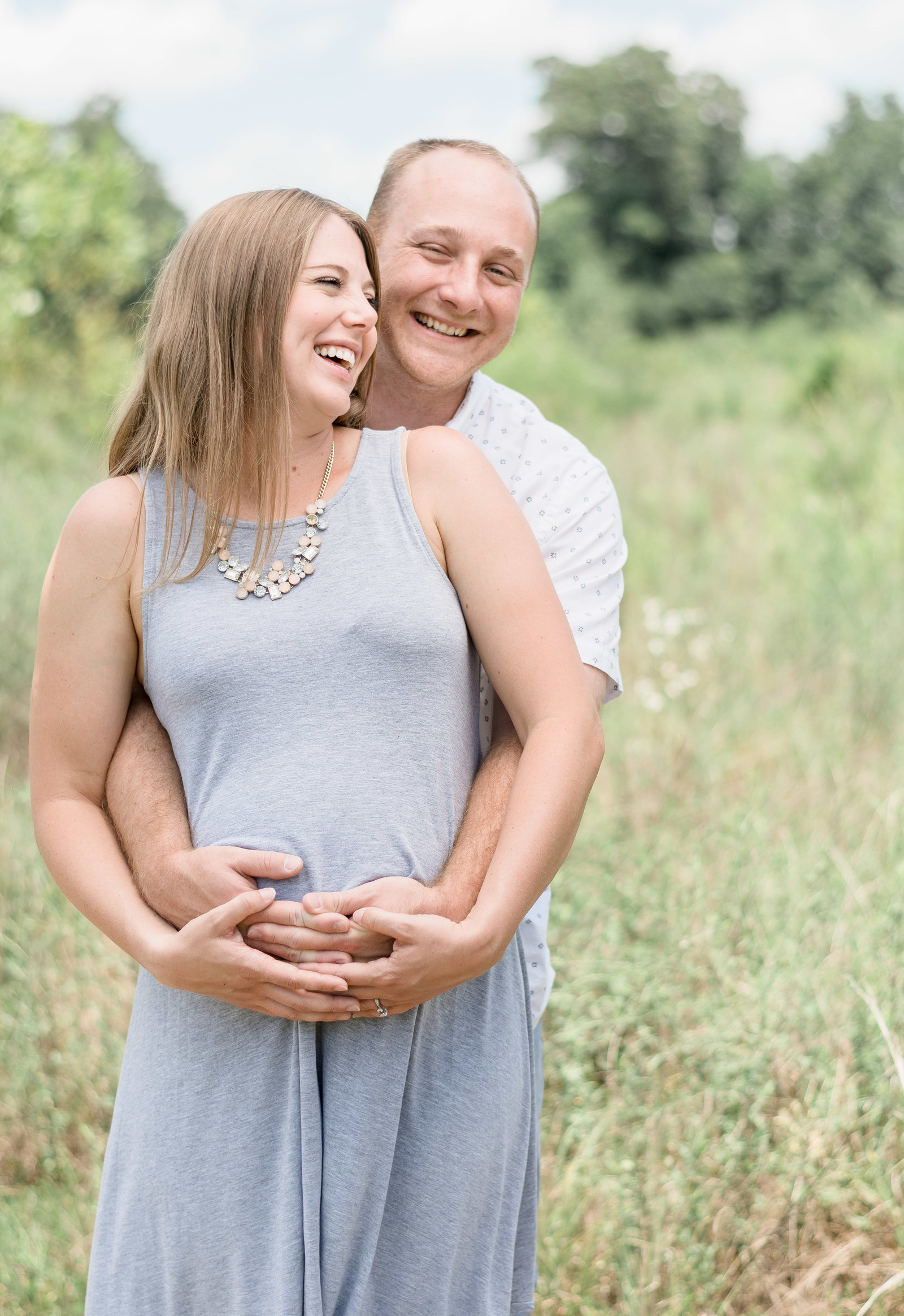 Charlotte Maternity photographer shot of couple on beach cute smiling in field in uptown charlotte