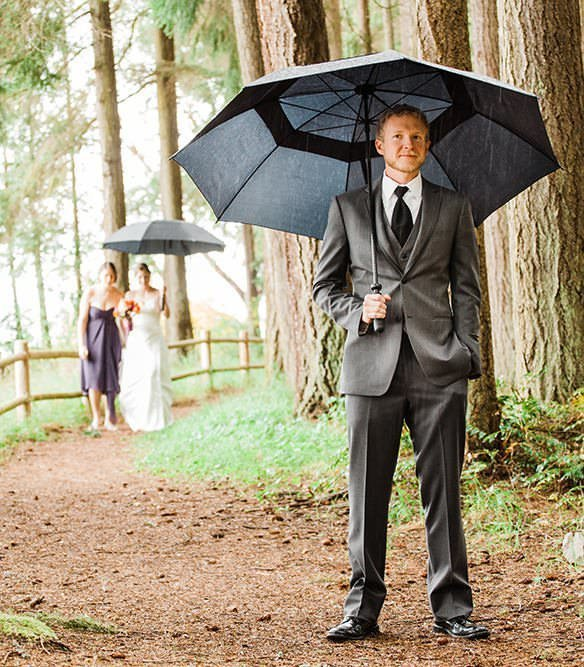 A groom waits for his bride under an umbrella on a rainy day in the Northwest