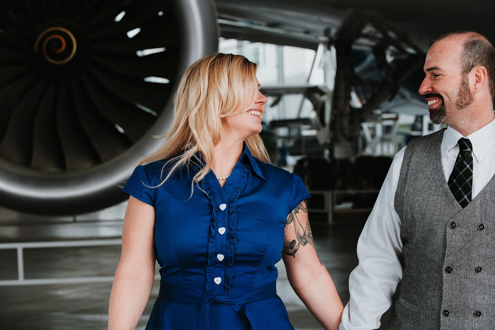 Couple holding hands in front of vintage plane by Cle Elum Engagement Photographer