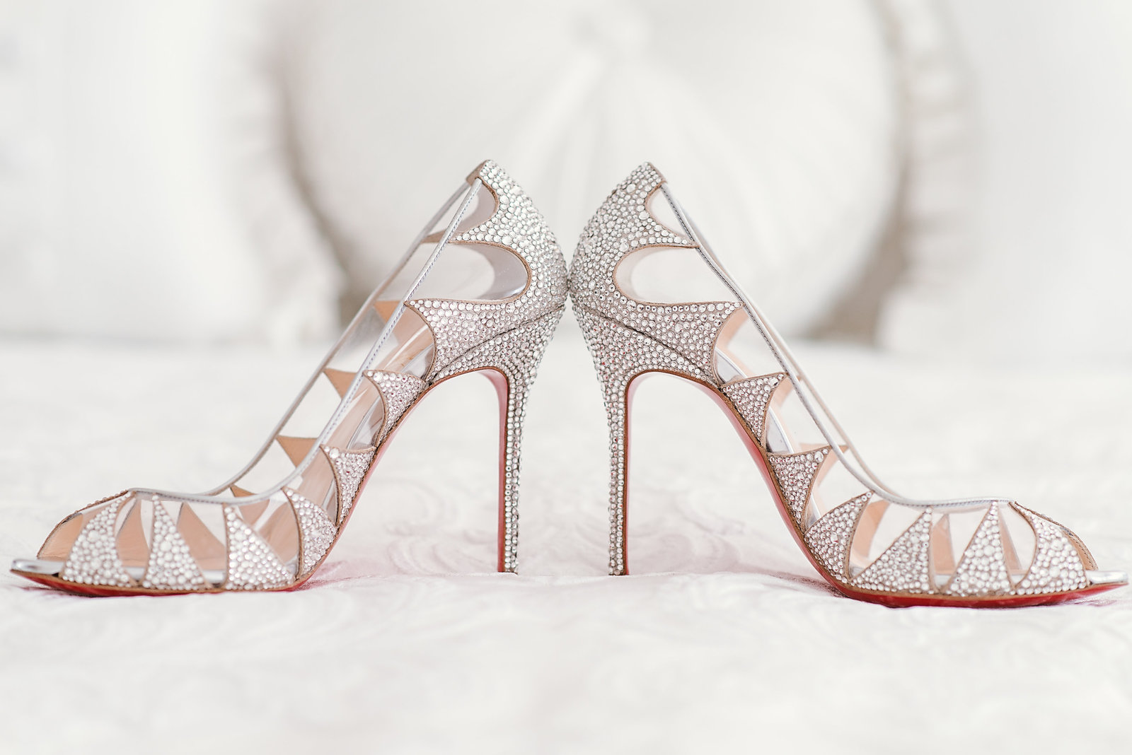 Wedding shoes  with red soles on bed