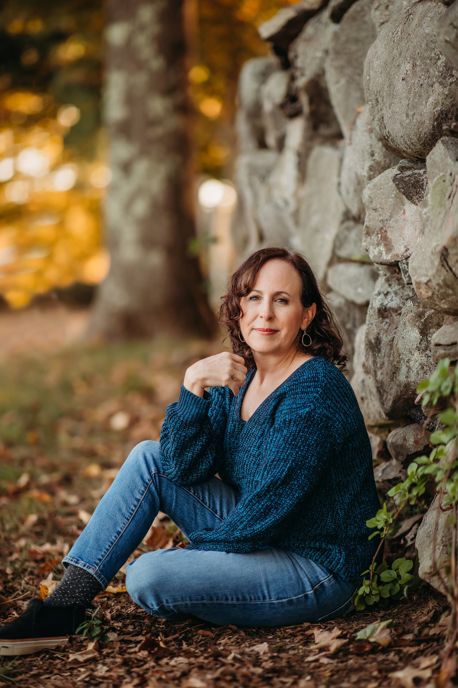 woman sits against rock wall in autumn for portrait session