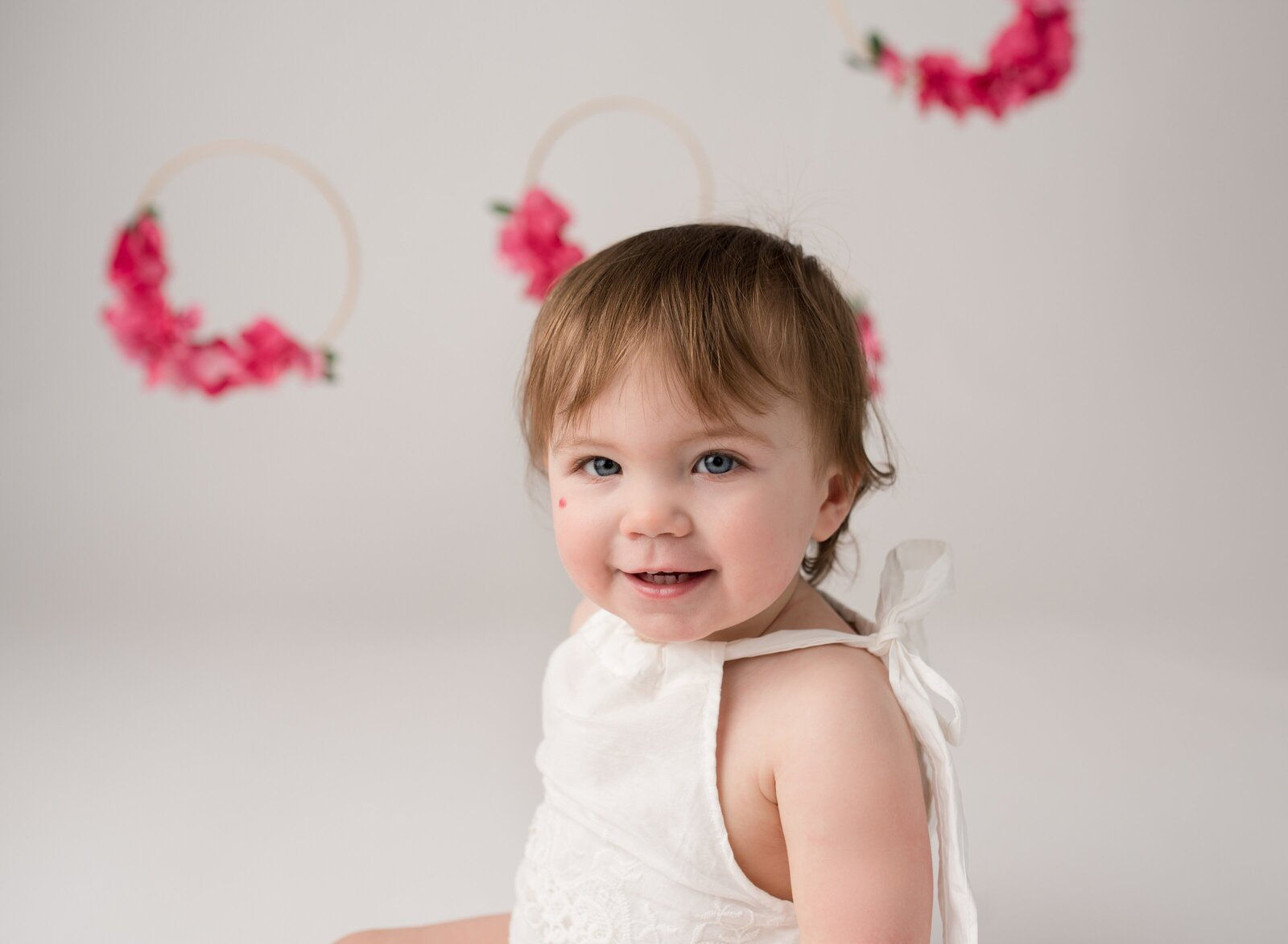 little girl in a white room and floral hoops smiling at the camera for her first birthday
