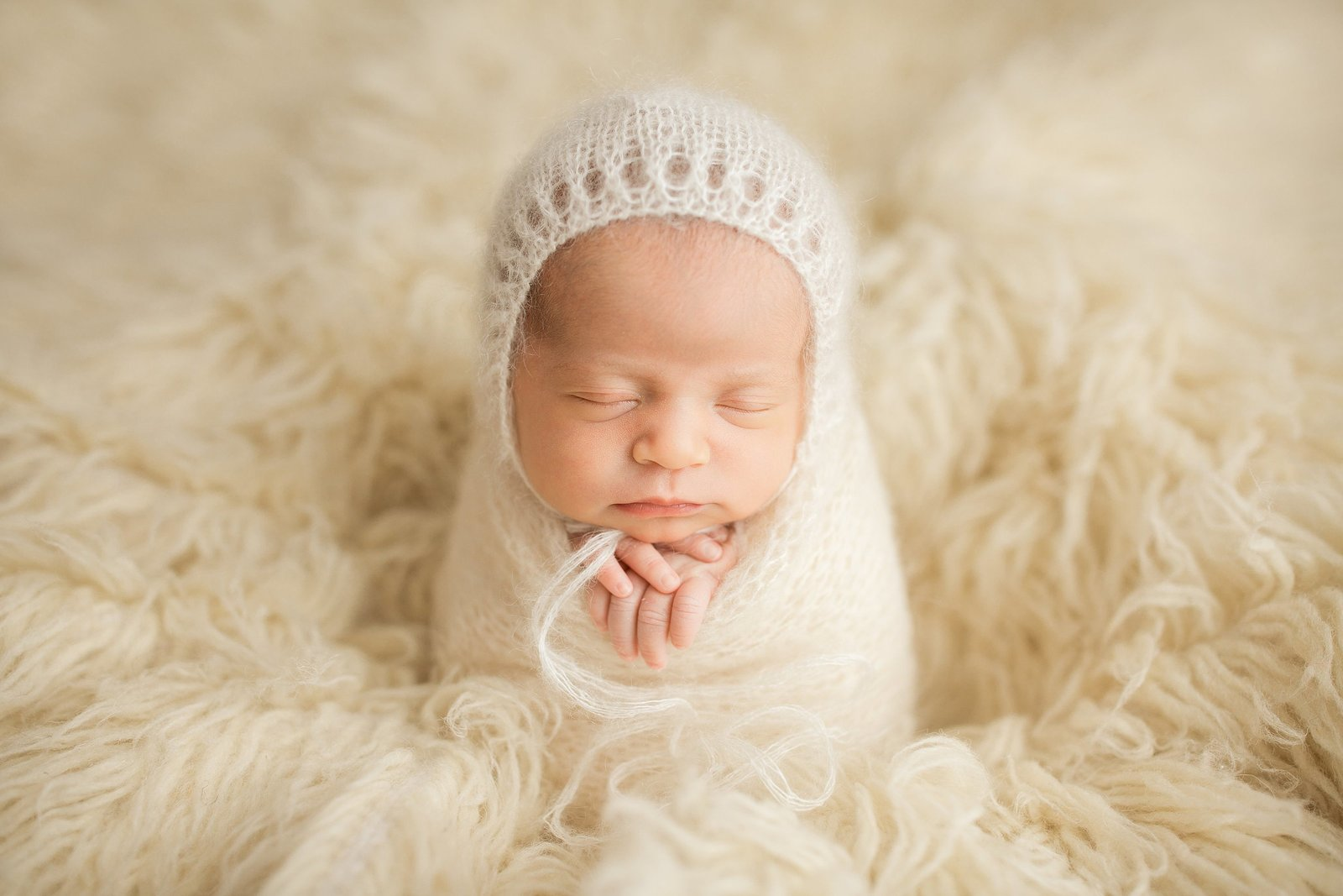 Newborn girl in ivory blanket